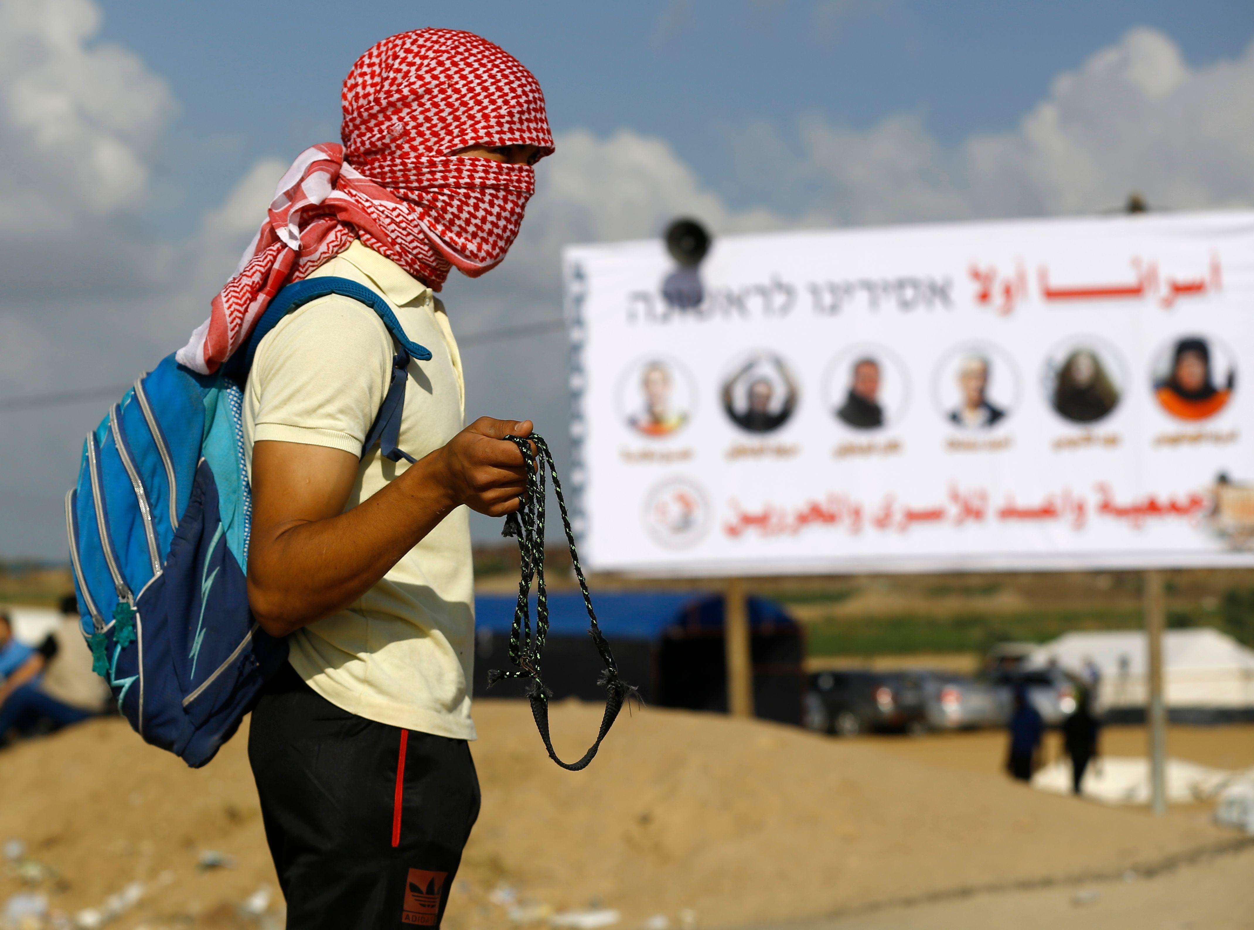 شاب فلسطينى يستعد لمواجهة قوات الاحتلال فى غزة