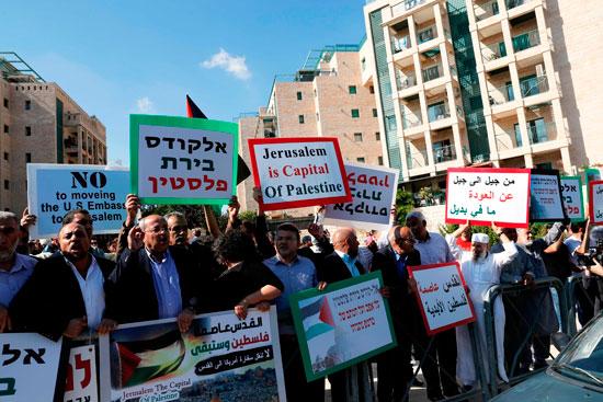 فلسطينيون يرفعون لوحات منددة بنقل السفارة الأمريكية