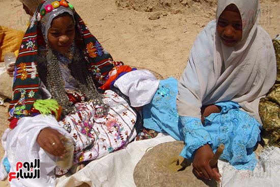 فتاتان يطحنان التوابل بالرحى الحجرى فى واحة أم الصغير