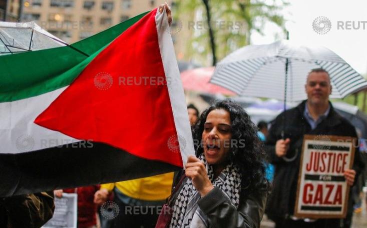 سيدة ترفع علم فلسطين خلال المظاهرات