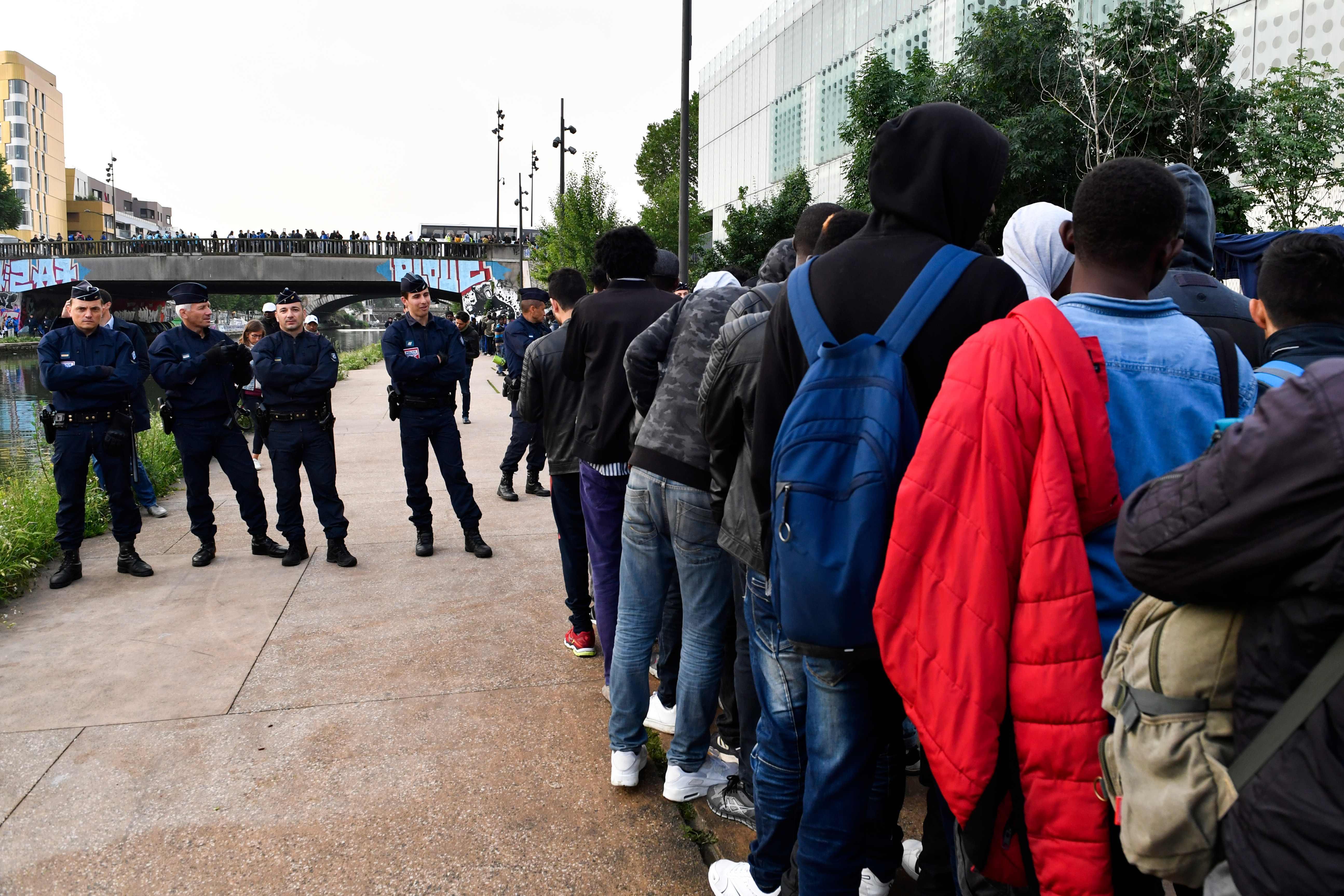 اصطفاف المهاجرين عقب اخلائهم من مخيمات بباريس