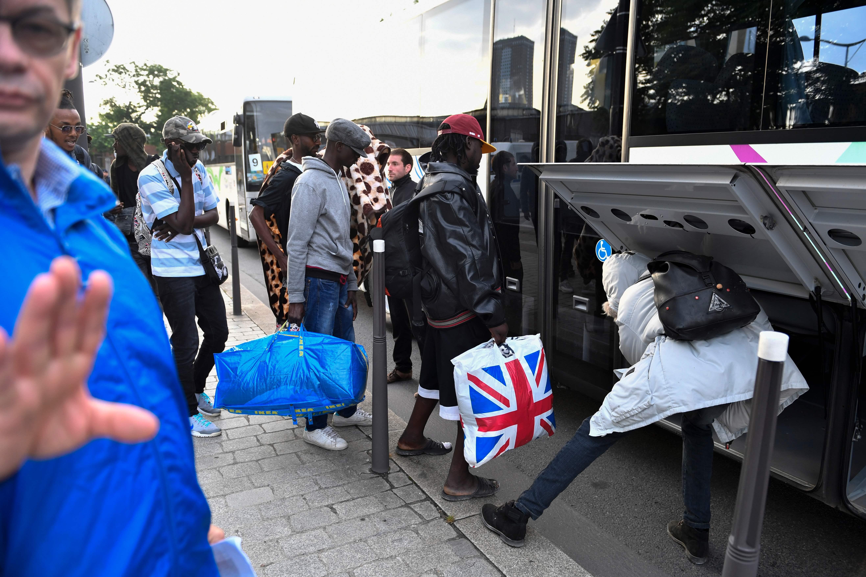مهاجرون يضعون أغراضهم فى أتوبيسات لنقلهم بباريس