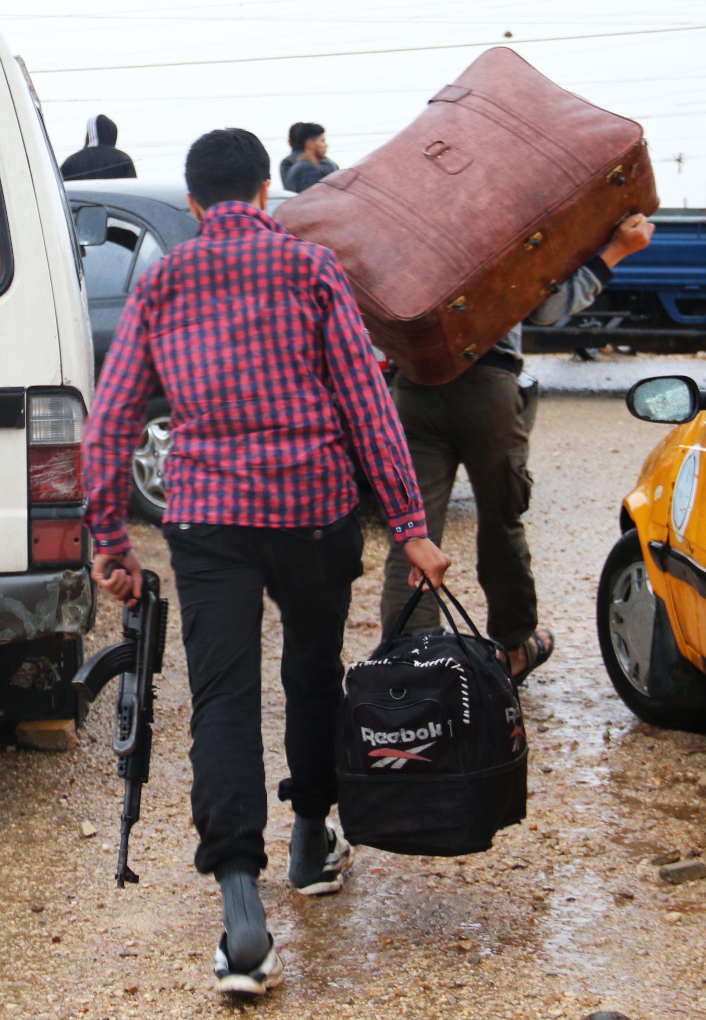 أحد المسلحين يحمل سلاحا وفى طريقه للمغادرة