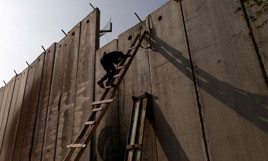 شاب فلسطينى يتسلق الجدار العازل للعبور إلى القدس المحتلة