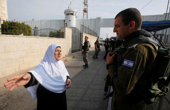 سيدة فلسطينية تقف أمام جندى إسرائيلى خلال عبورها نقطة تفتيش