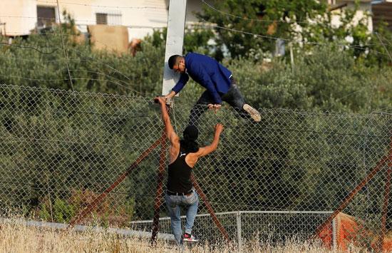 شبان فلسطينيين يتسلقون الحواجز الحديدية للعبور إلى القدس