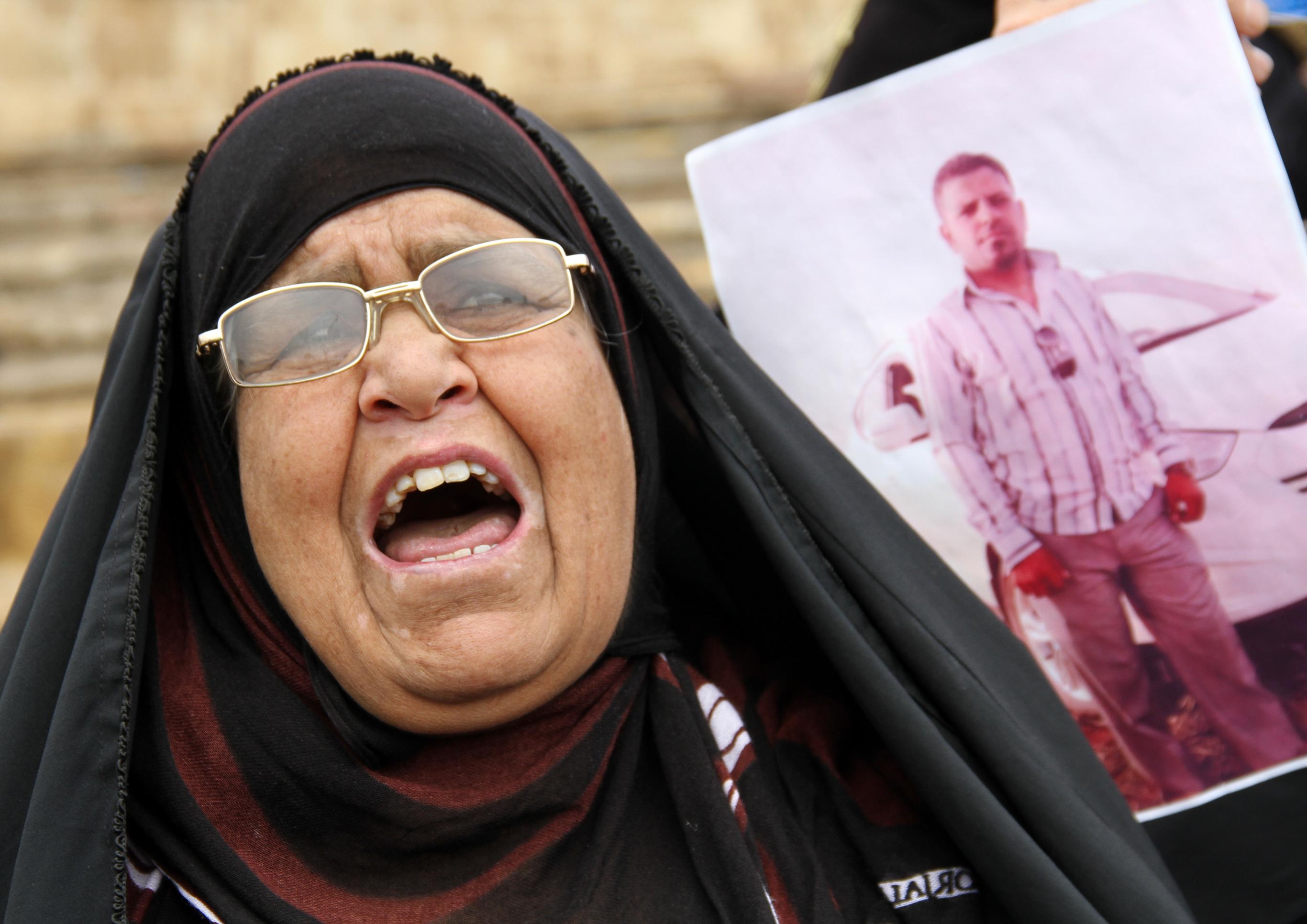 امرأة تحمل صورة ابنها