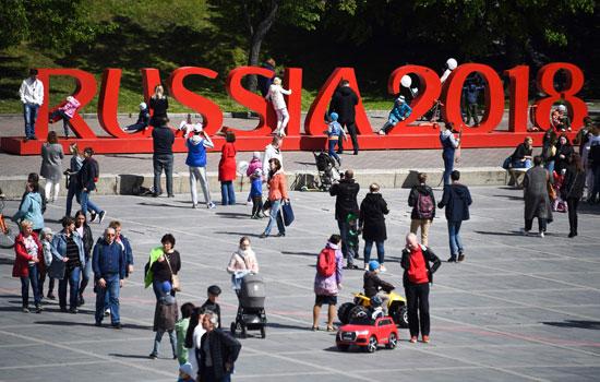 """الزائرون يلتقطون الصور بجوار لافتة """"روسيا 2018"""""""
