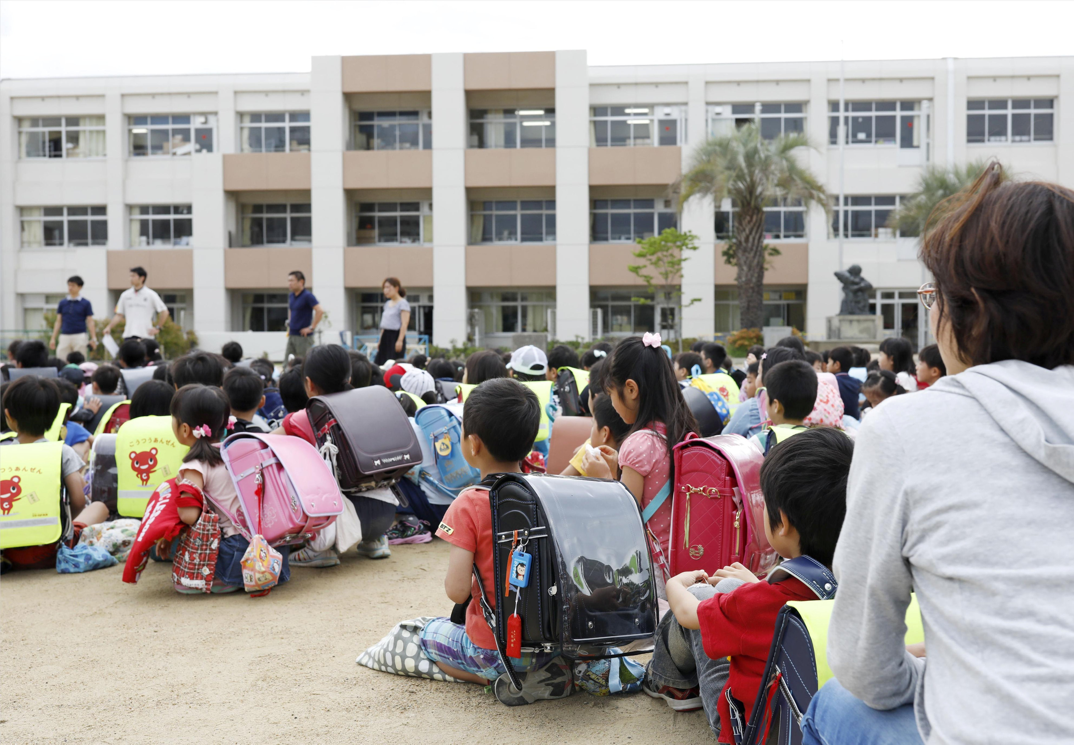 أطفال يابانيين فى ملعب مدرستهم بعد إخلاء الفصول