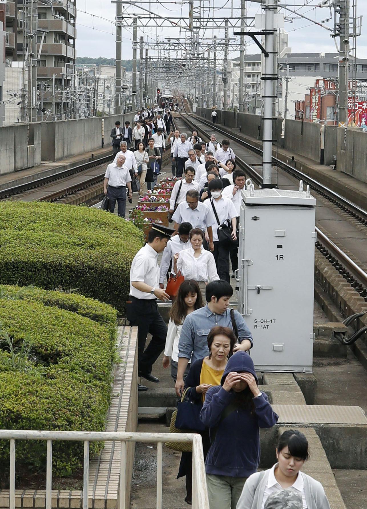 مواطنين يترجلون على السكك الحديدية بعد إخلاء القطارات