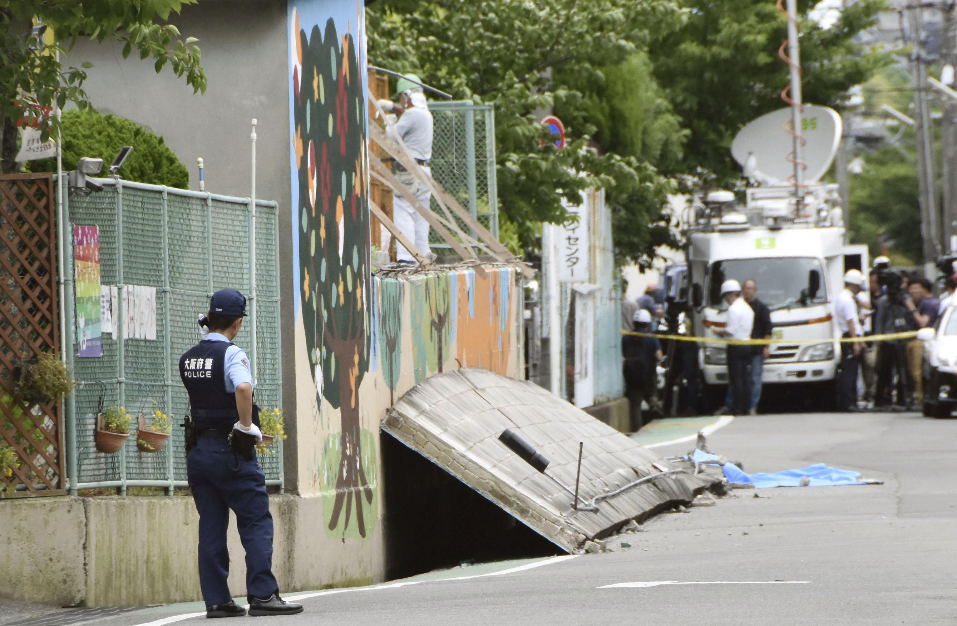 ضابط يابانى يتابع الموقف بعد سقوط حائط على فتاة أدى إلى وفاتها