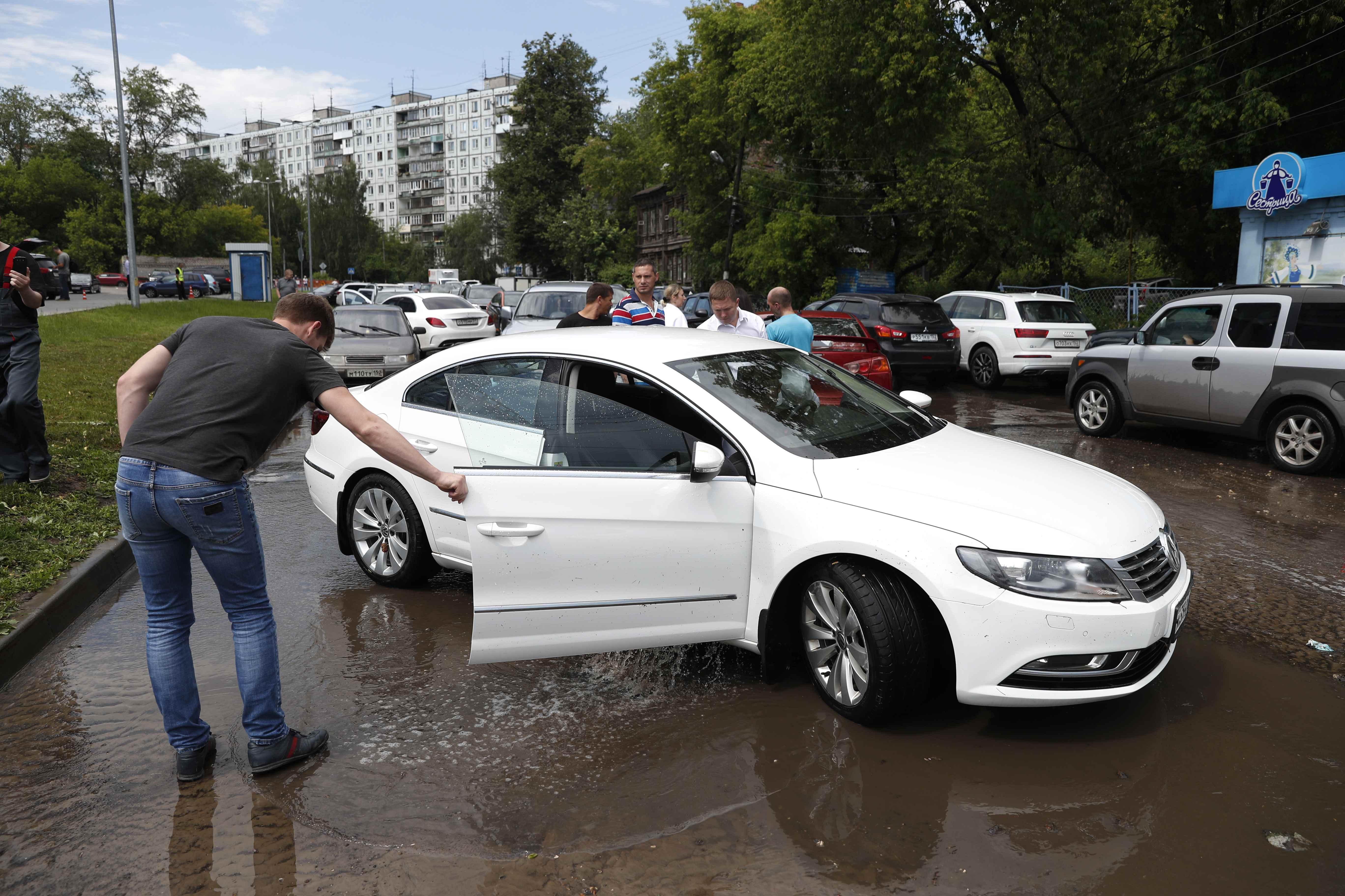 مواطن روسى يتابع حالة سيارته بعد الأمطار