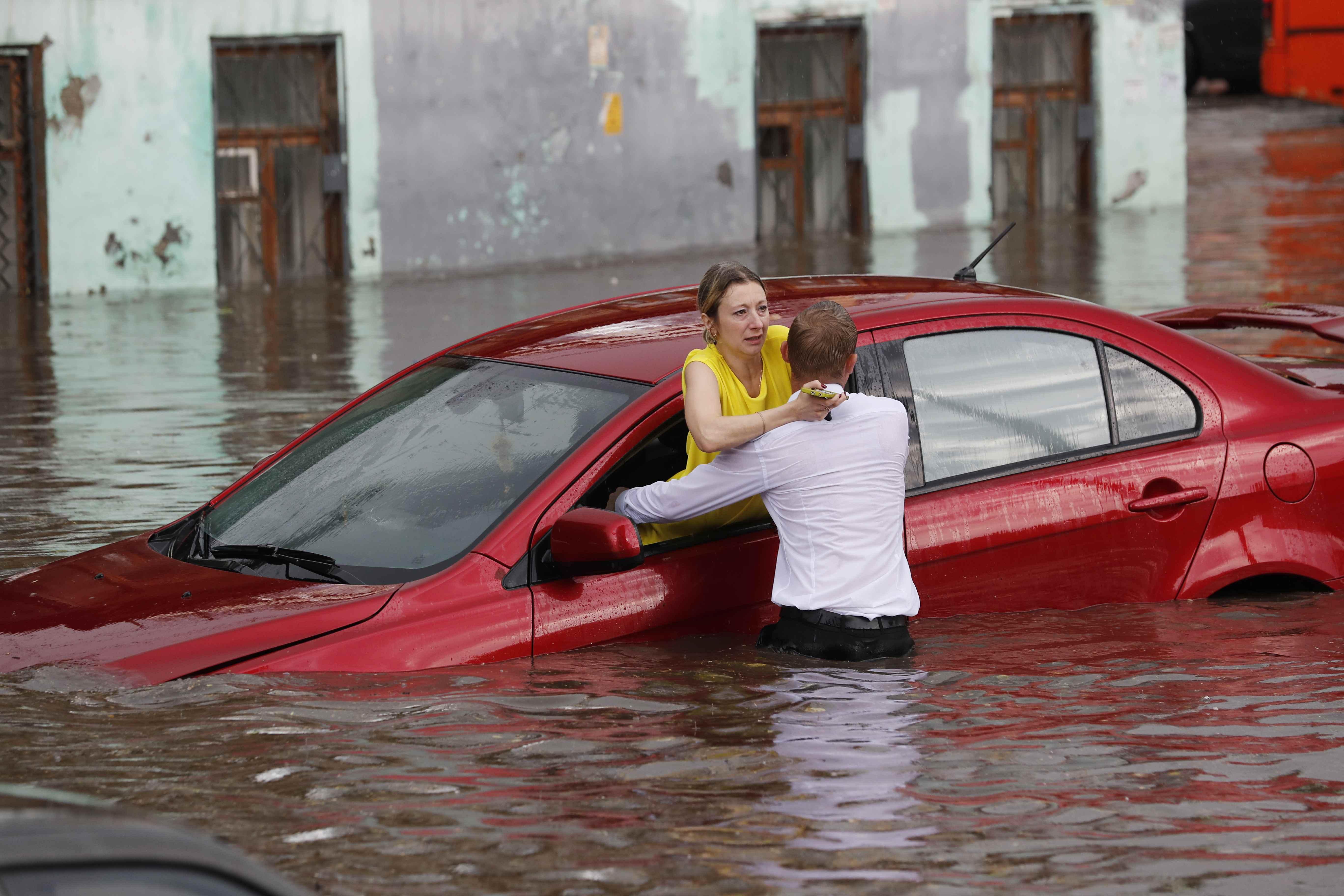 أحد المنقذين يساعد سيدة على الخروج من سيارتها