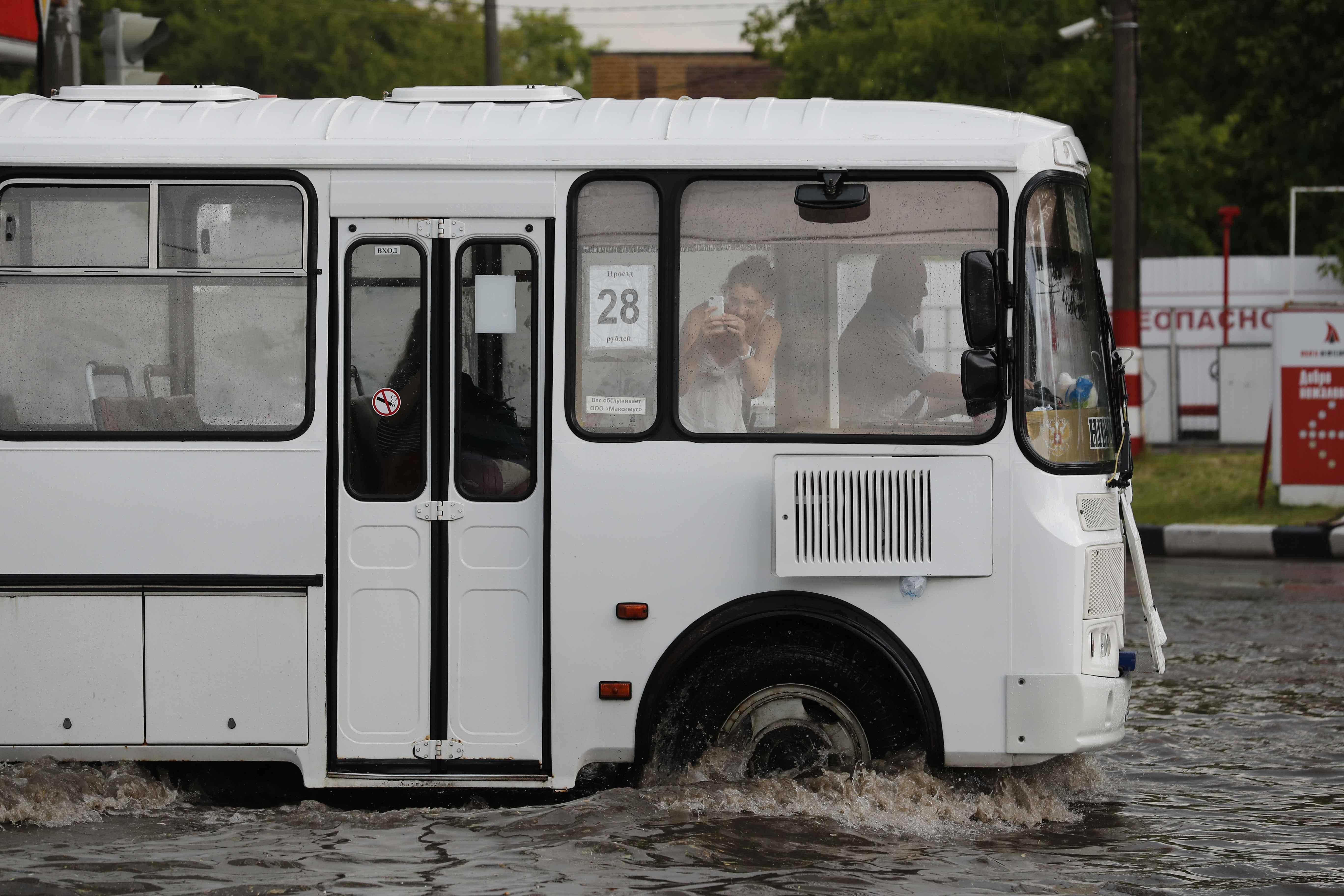 إمرأة تلتقط صورة عبر المحمول للشوارع الغارقة بالمياه