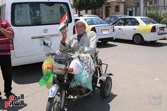 أحد ذوي الإحتياجات الخاصة يرفع علام جمهورية مصر العربية ابتهاجا بحلف الرئيس لليمين