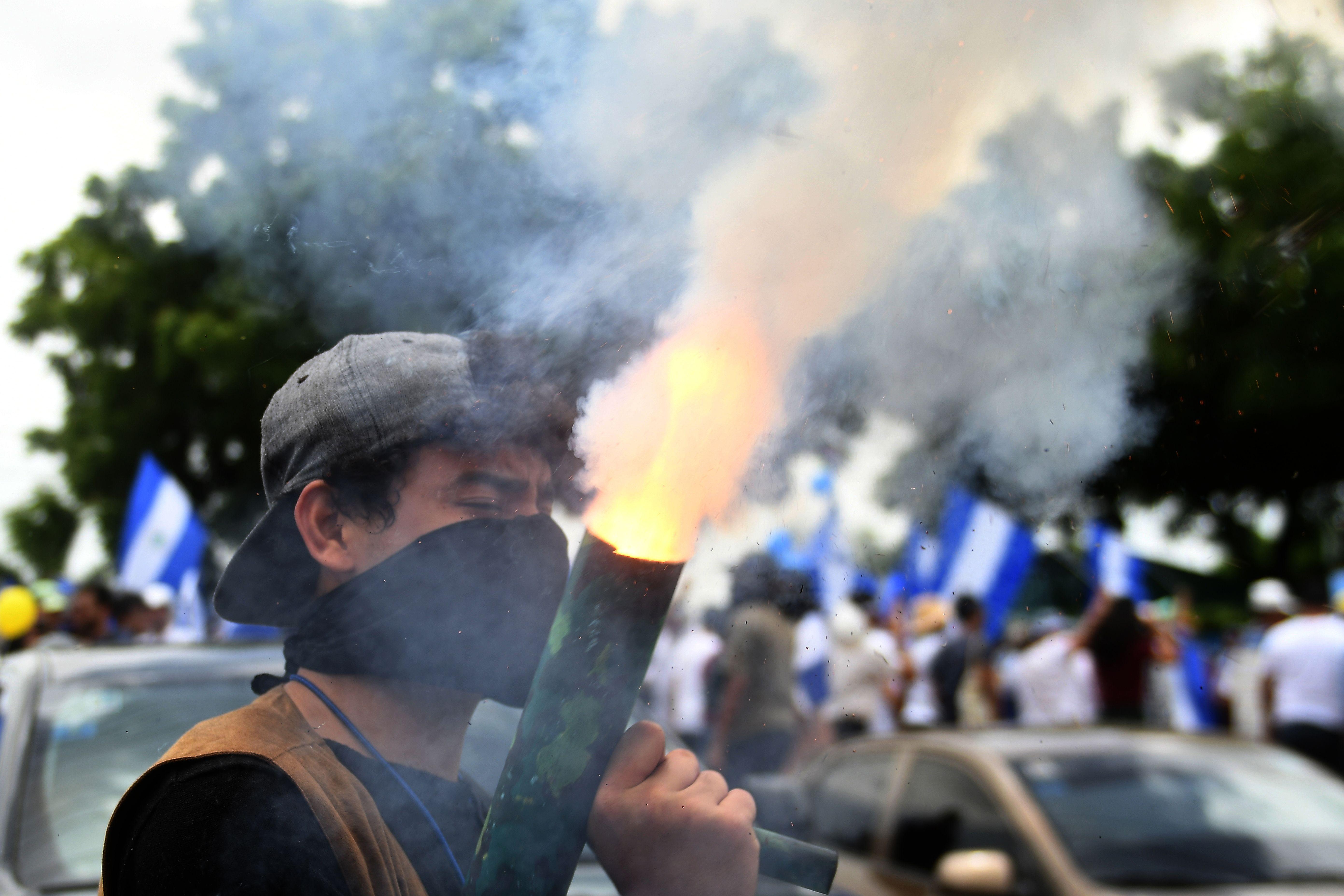 متظاهر يطلق قذيفة خلال الاحتجاجات