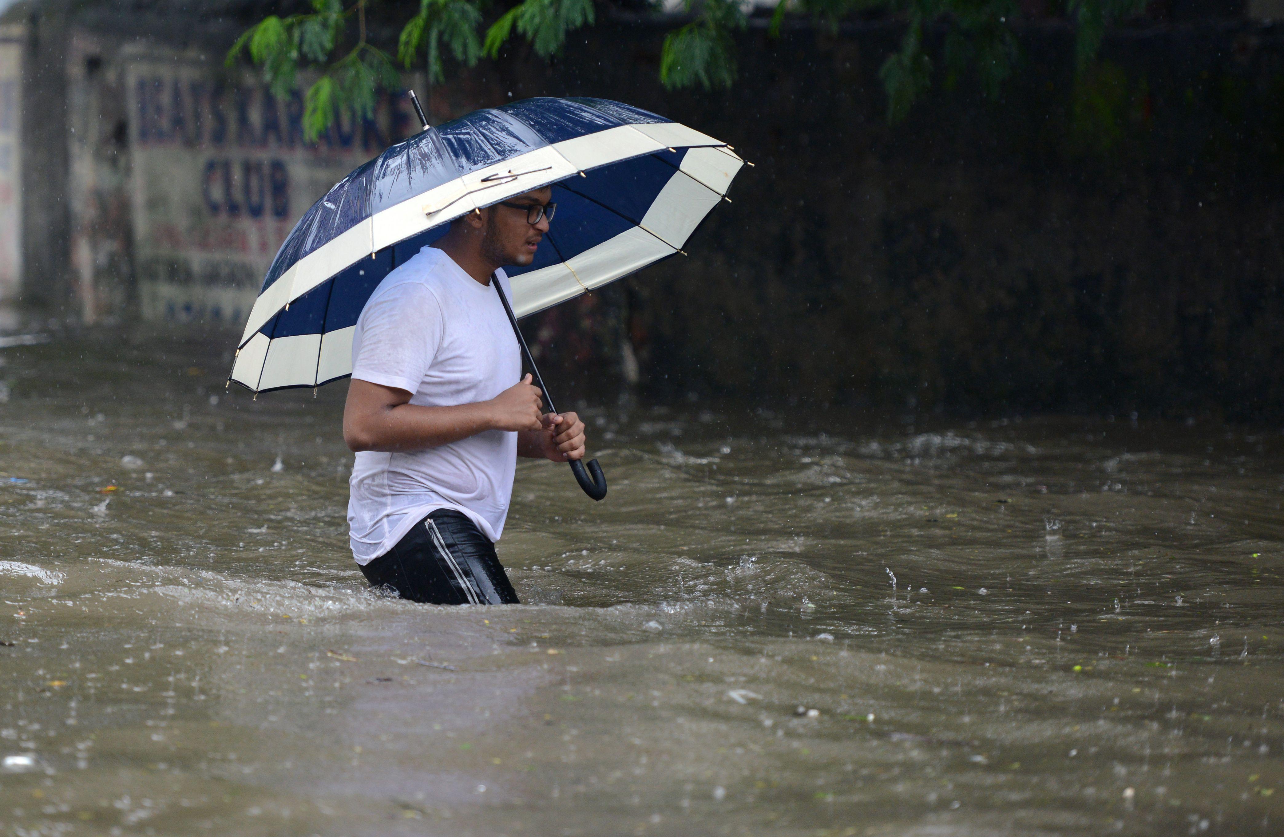 مواطن يحمل الشمسية خلال الأمطار