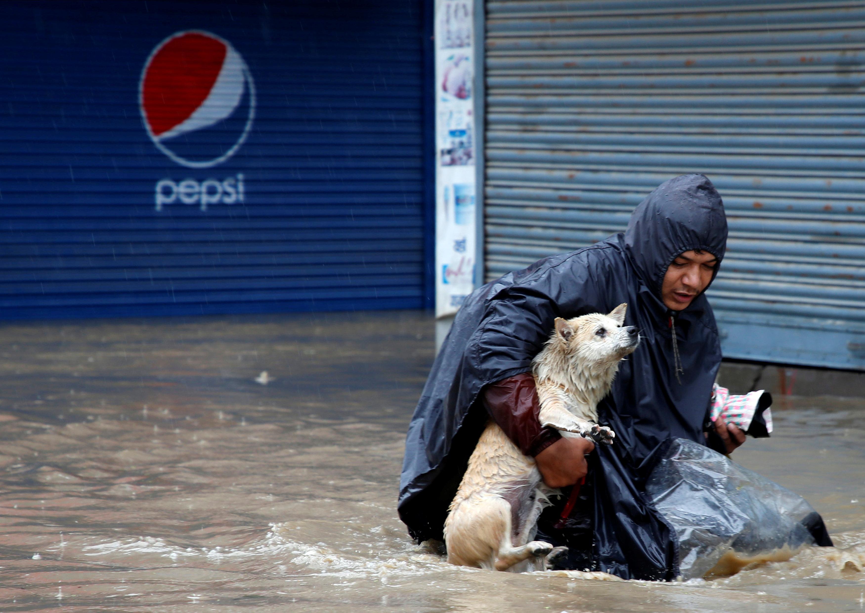 مواطن يحاول إنقاذ كلبه من الفيضانات