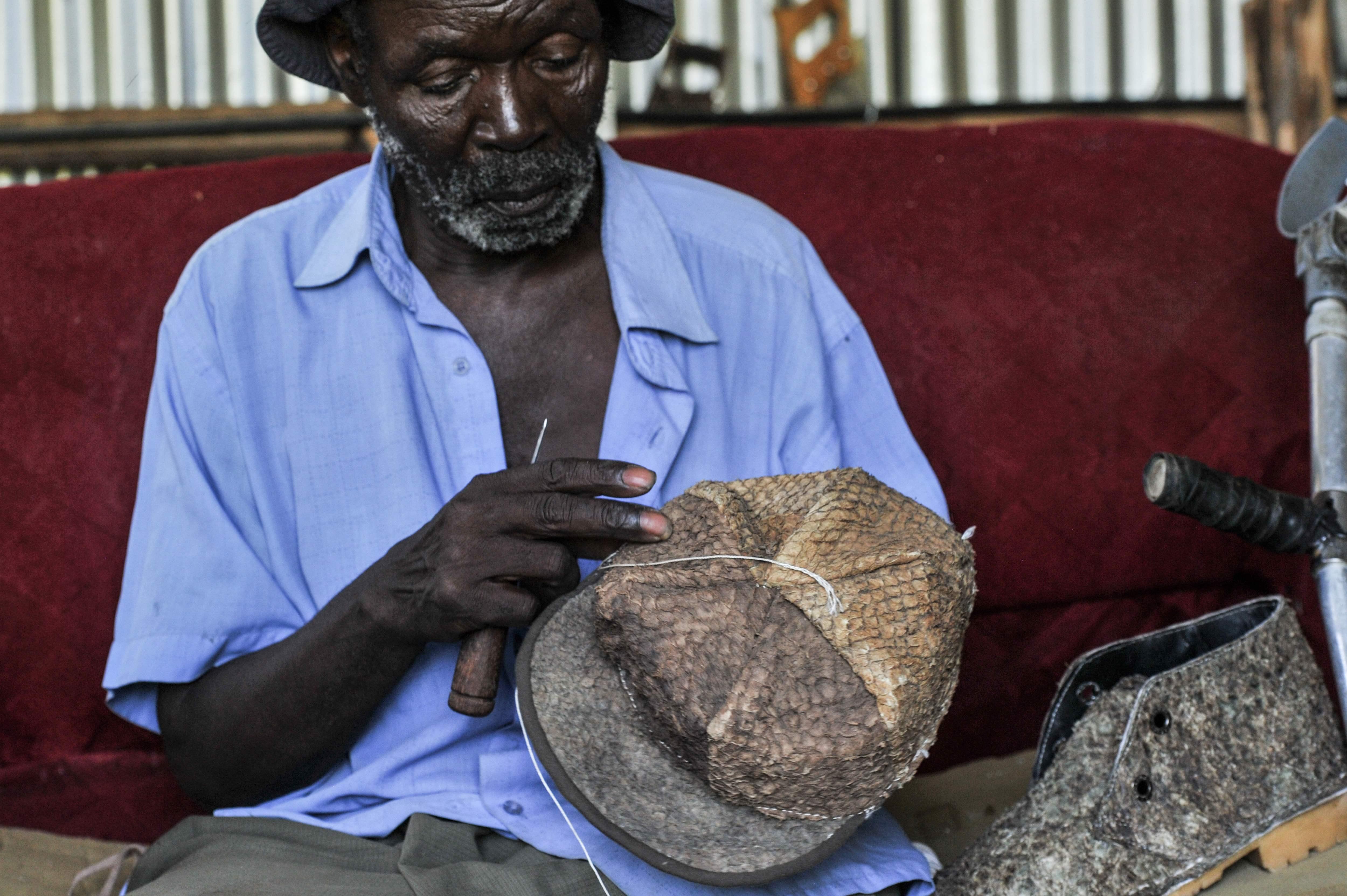 رجل يصمع قبعة وحذاء من جلد السمك