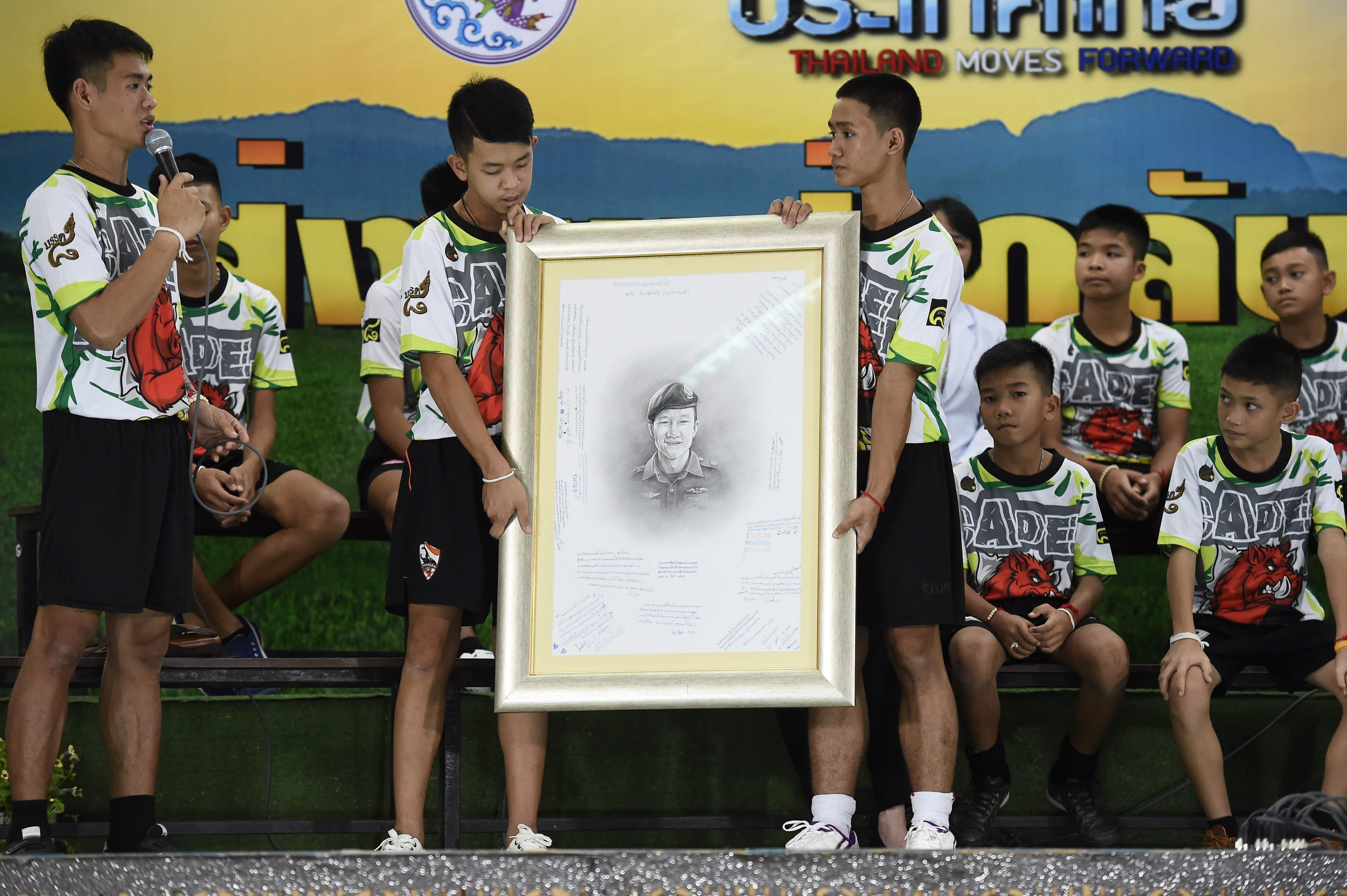 أطفال الكهف يحملون صورة لغواض توفى أثناء انقاذهم