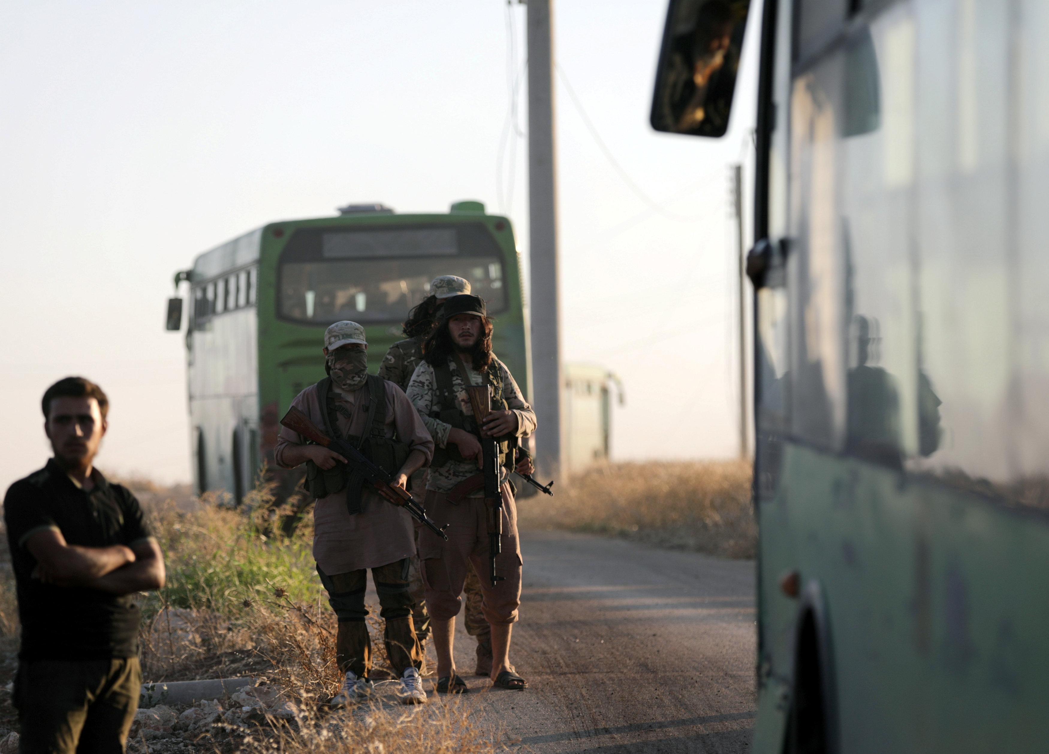 مسلحين بجوار الباصات