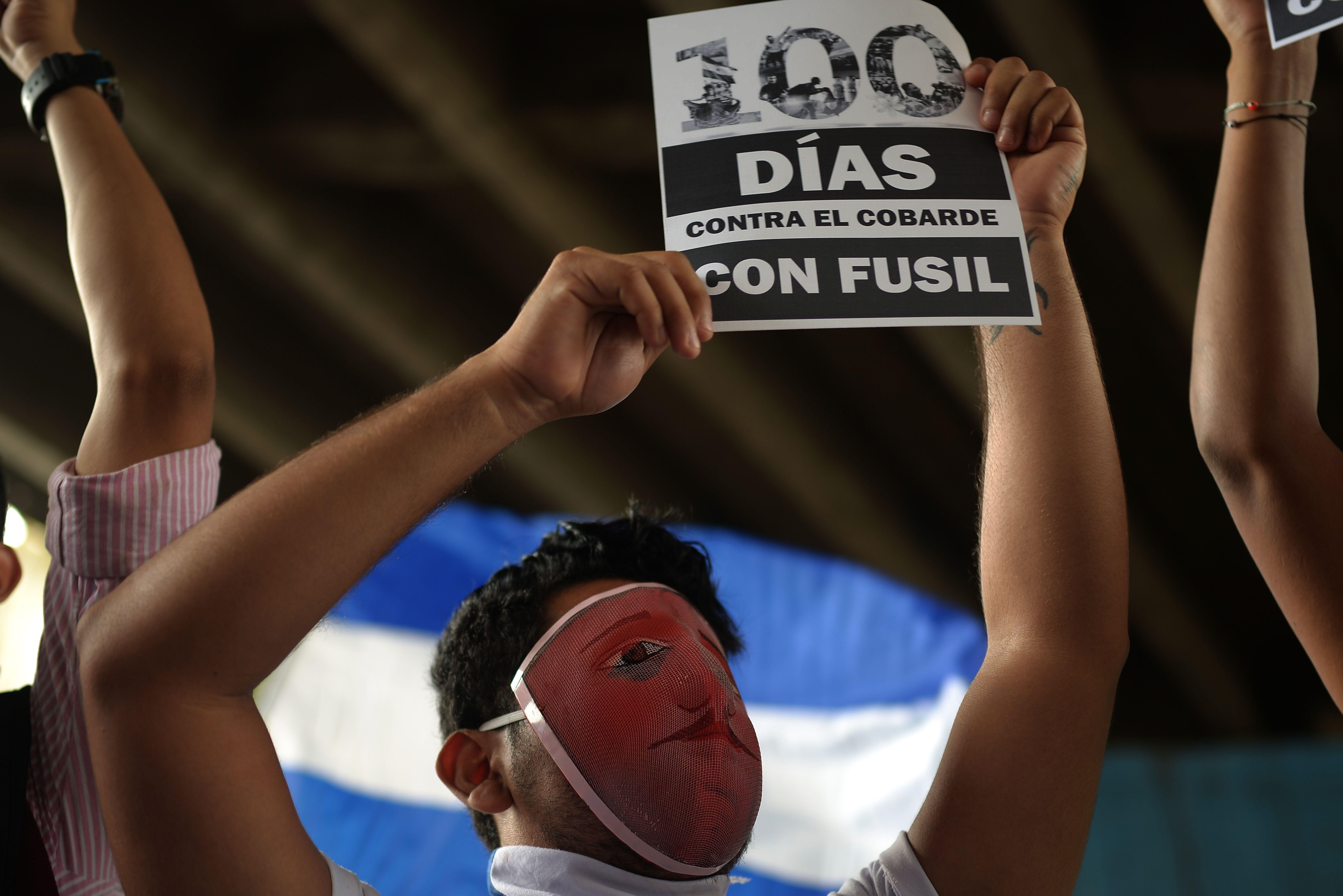متظاهر يرفع لافتة 100 يوم من الاحتجاج