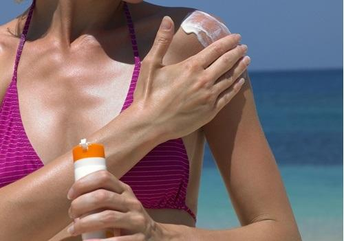 woman-putting-on-sunscreen
