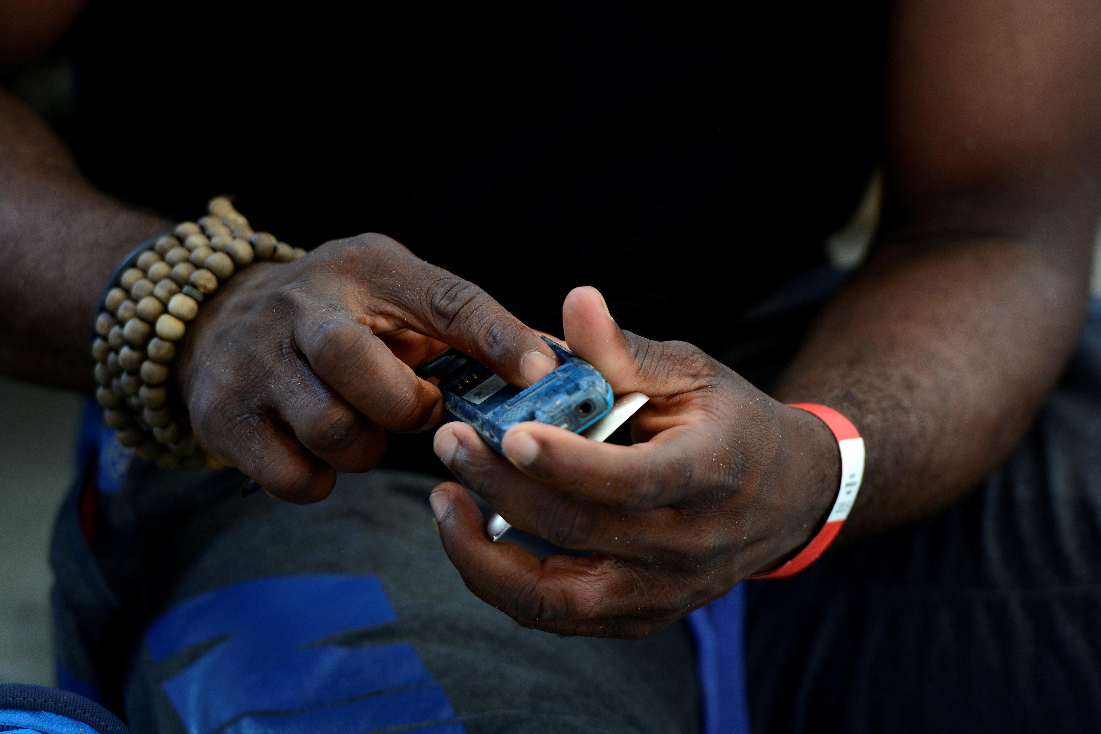 احد المهاجرين أثناء فحص هاتفه المحول بعد إنقاذه