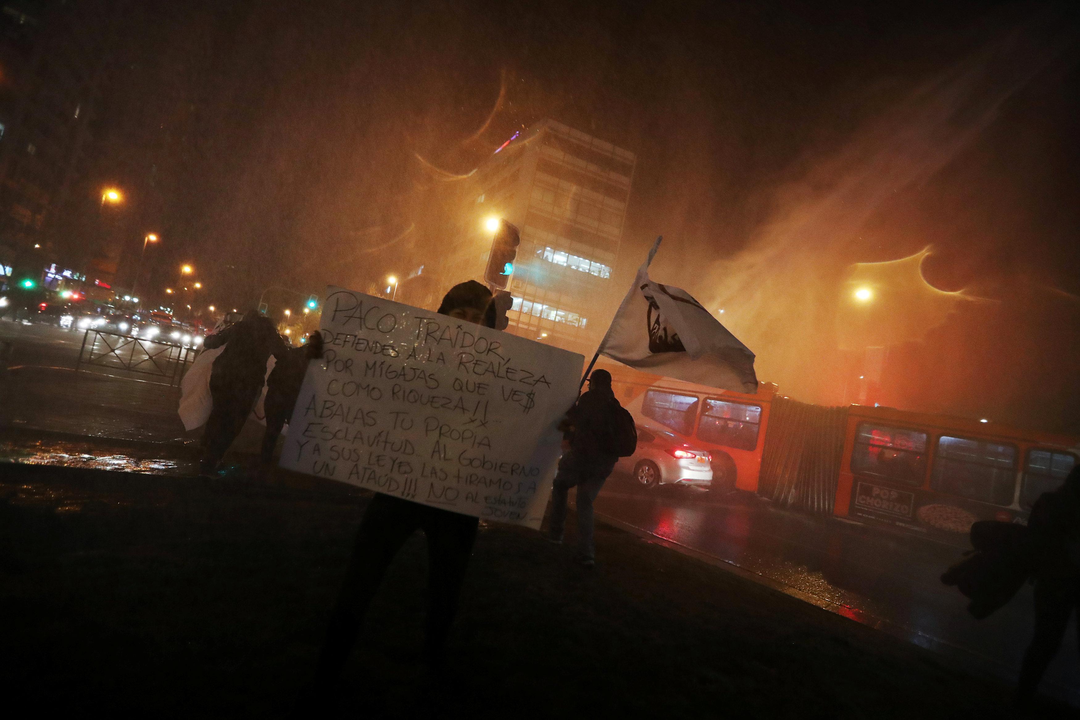 أحد المتظاهرين يحمل لافتة ضد الرئيس