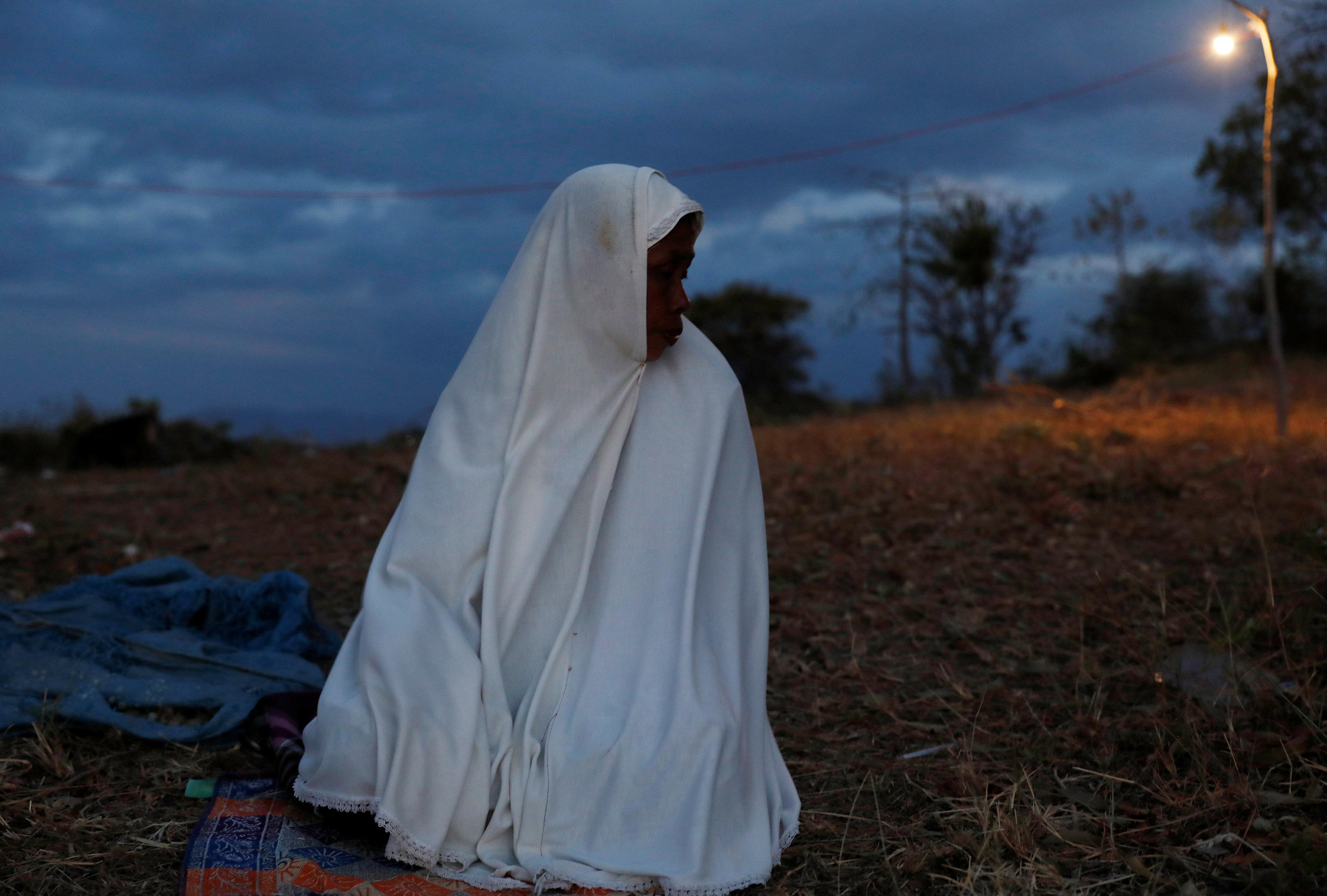 امرأة تصلى في مأوى مؤقت فوق أحد التلال فى شاطئ سينجيجى خوفا من تسونامى