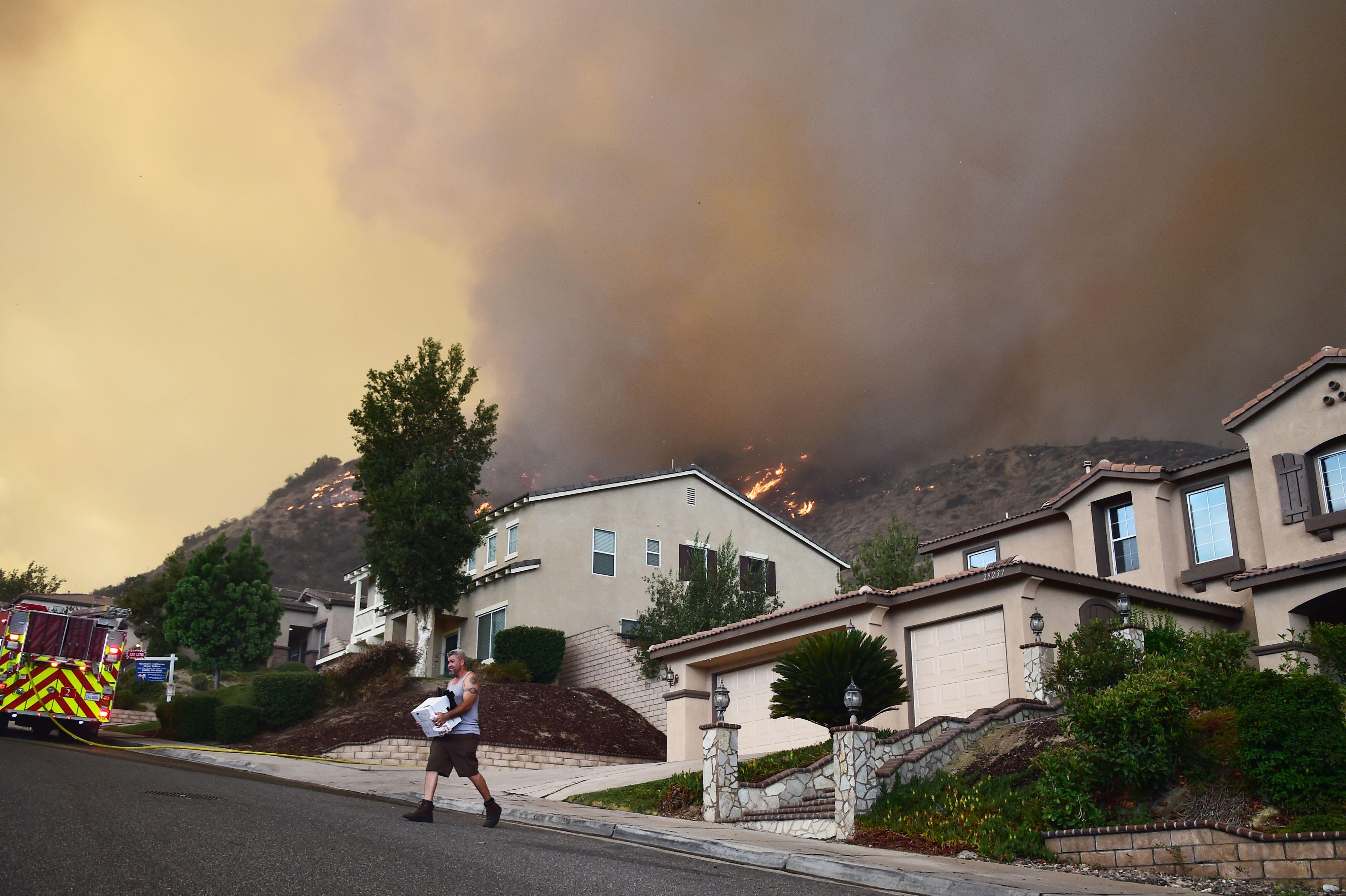 رجل يحمل متعلقاته ويهرب بها قبل وصول الحرائق لمنزله