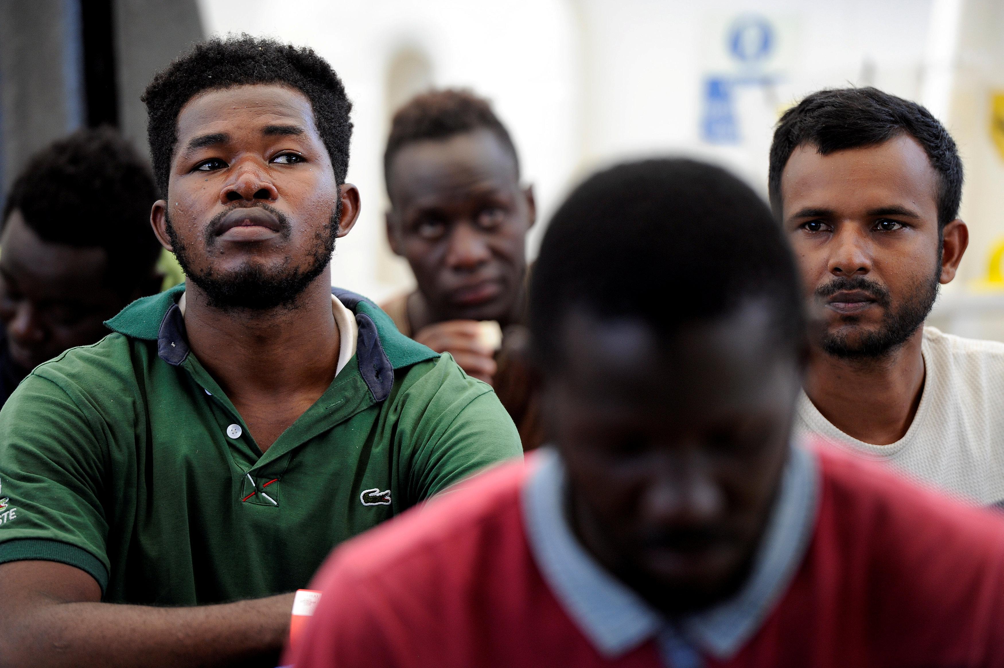 المهاجرين أثناء الاستماع لخطاب الترحيب