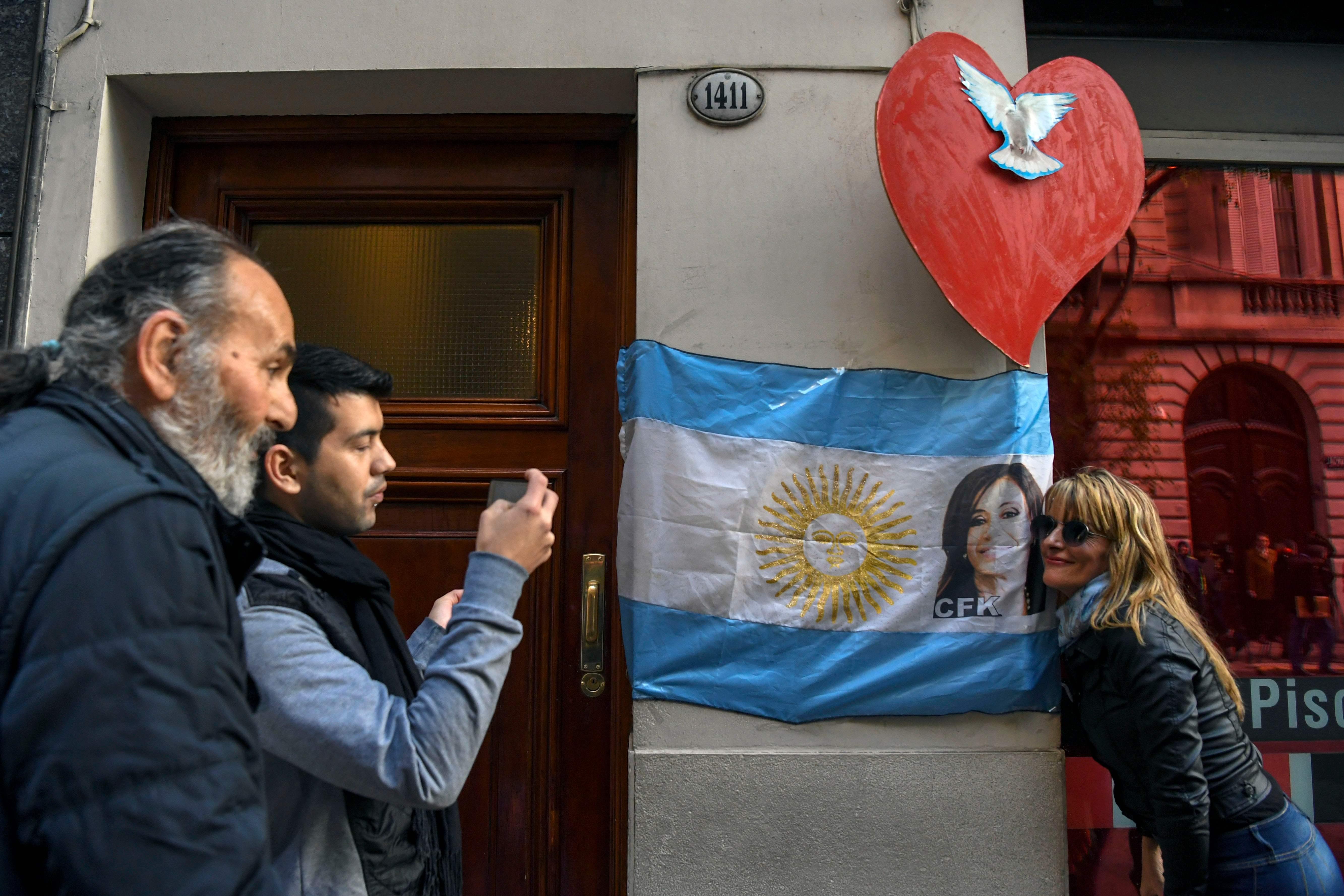 سيدة تلتقط صورة مع علم الارجنتين عليه صورة الرئيس السابق