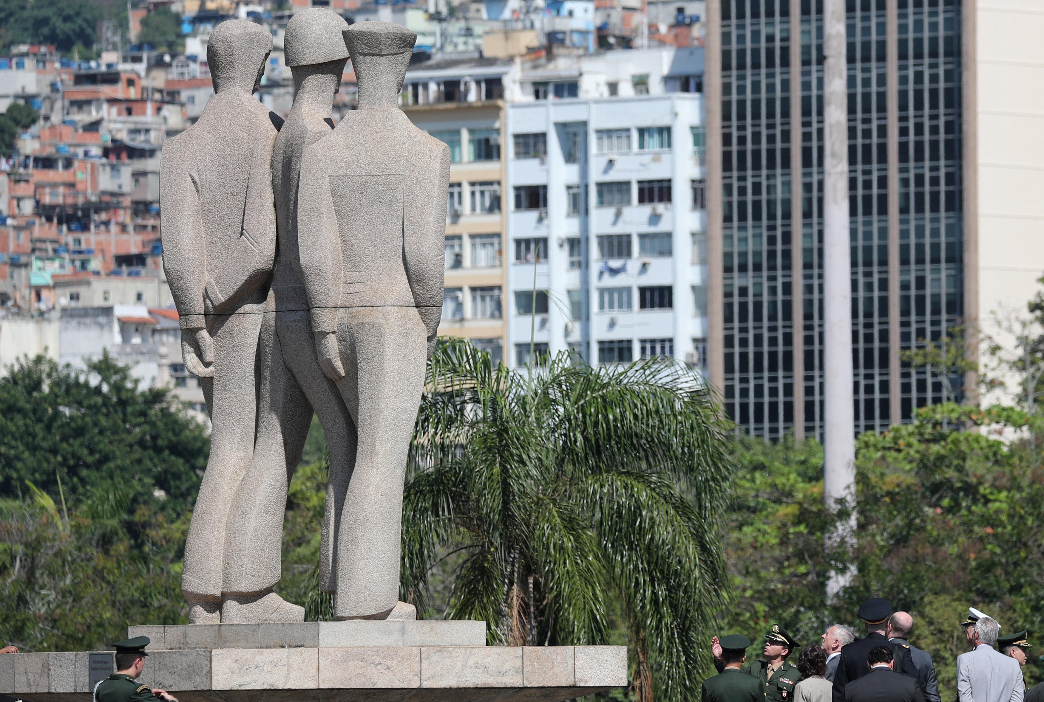 ماتيس ينظر إلى نصب قتلى الحرب العالمية الثانية مع الأحياء الفقيرة في مدينة ريو أمارو في الخلفية