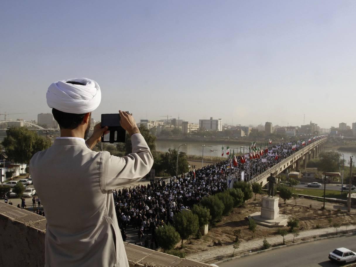 رجل دين إيرانى يصور مظاهرة أعلى أحد الجسور فى إيران