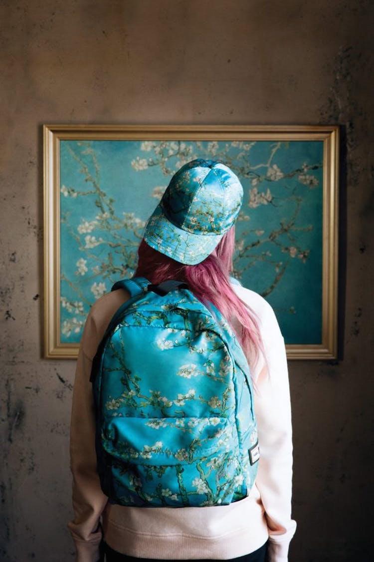 شابة ترتدى طاقية و حقيبة ظهر و تقف أمام لوحة لفان جوخ بنفس اللوحة