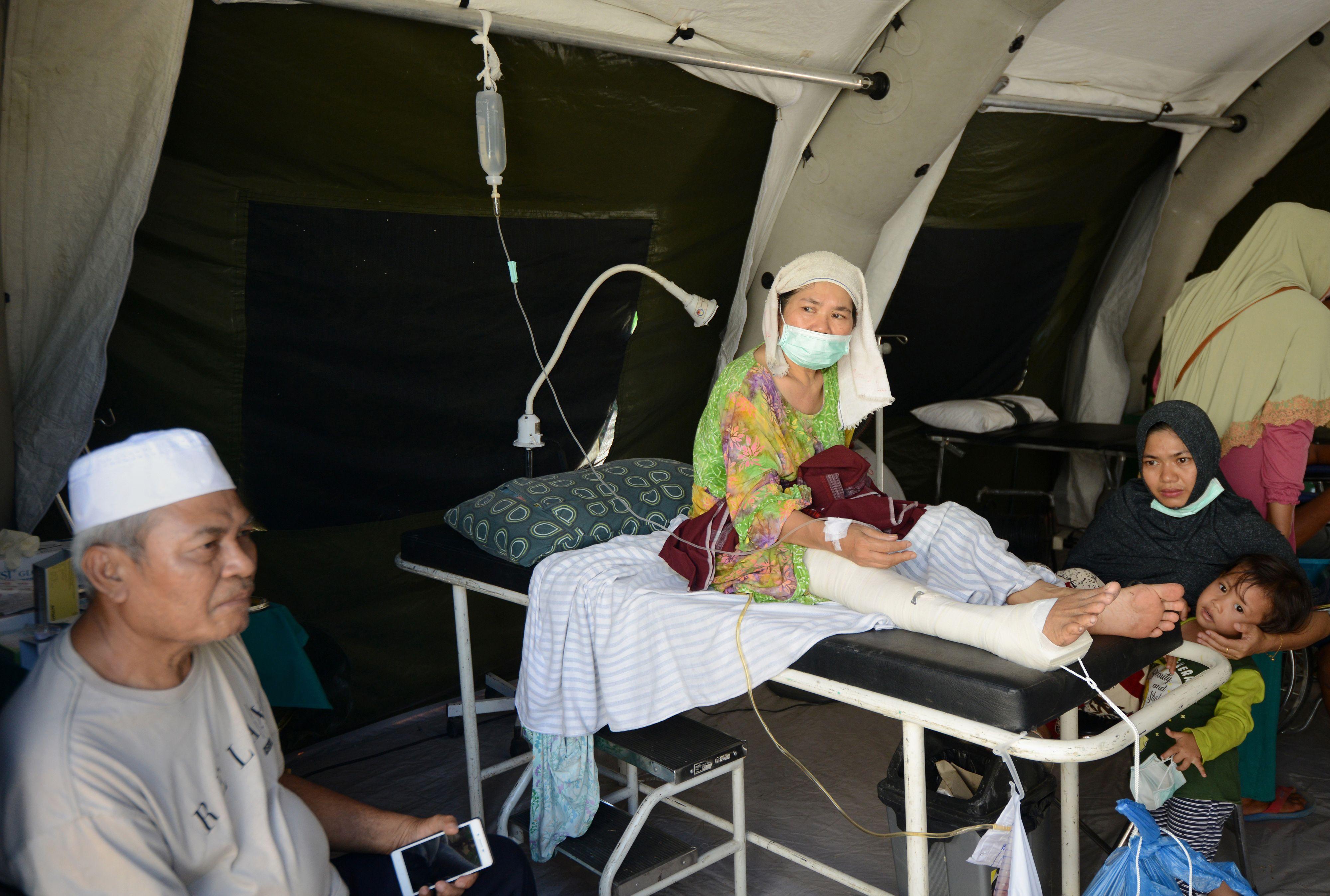 مصابه محاطة بأفراد أسرتها بعد الزلزال المدمر