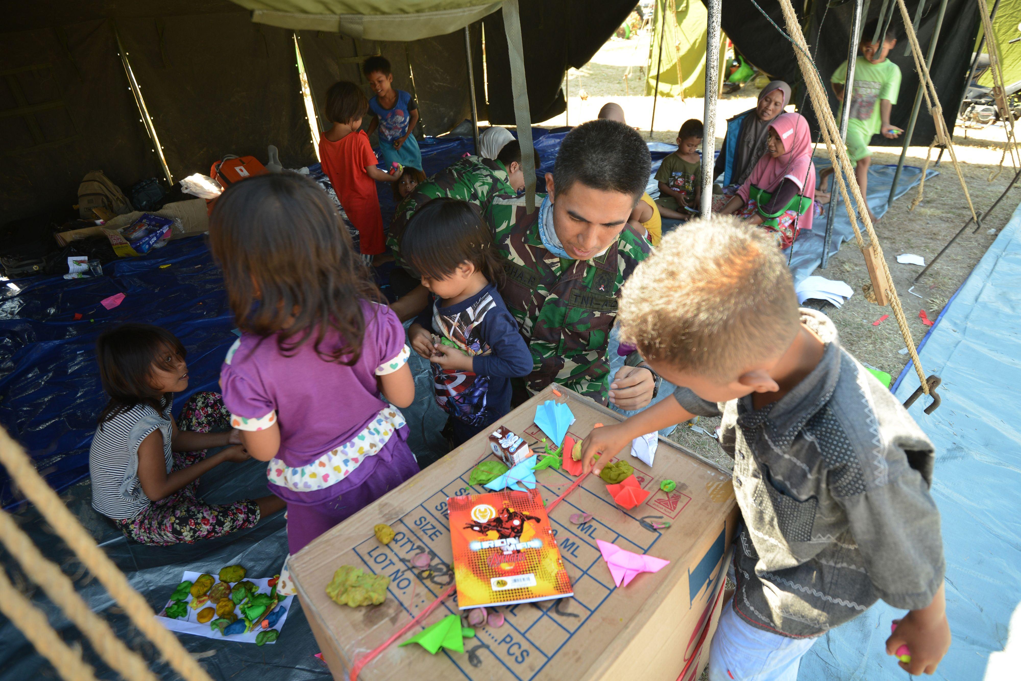 أطفال يلعبون بمشاركة أحد عناصر الإسعاف