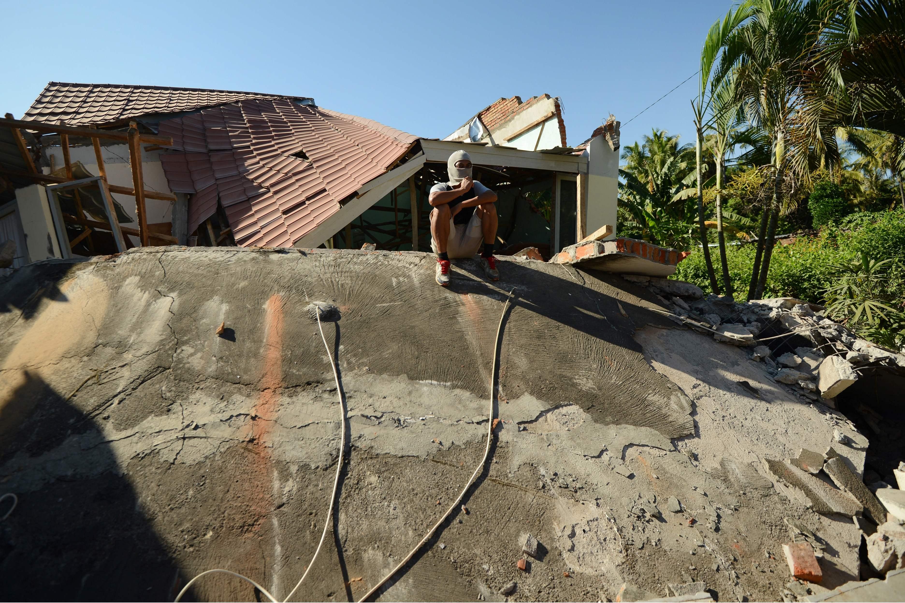 مواطن أندونيسى يجلس على أنقاض منزله المهدم