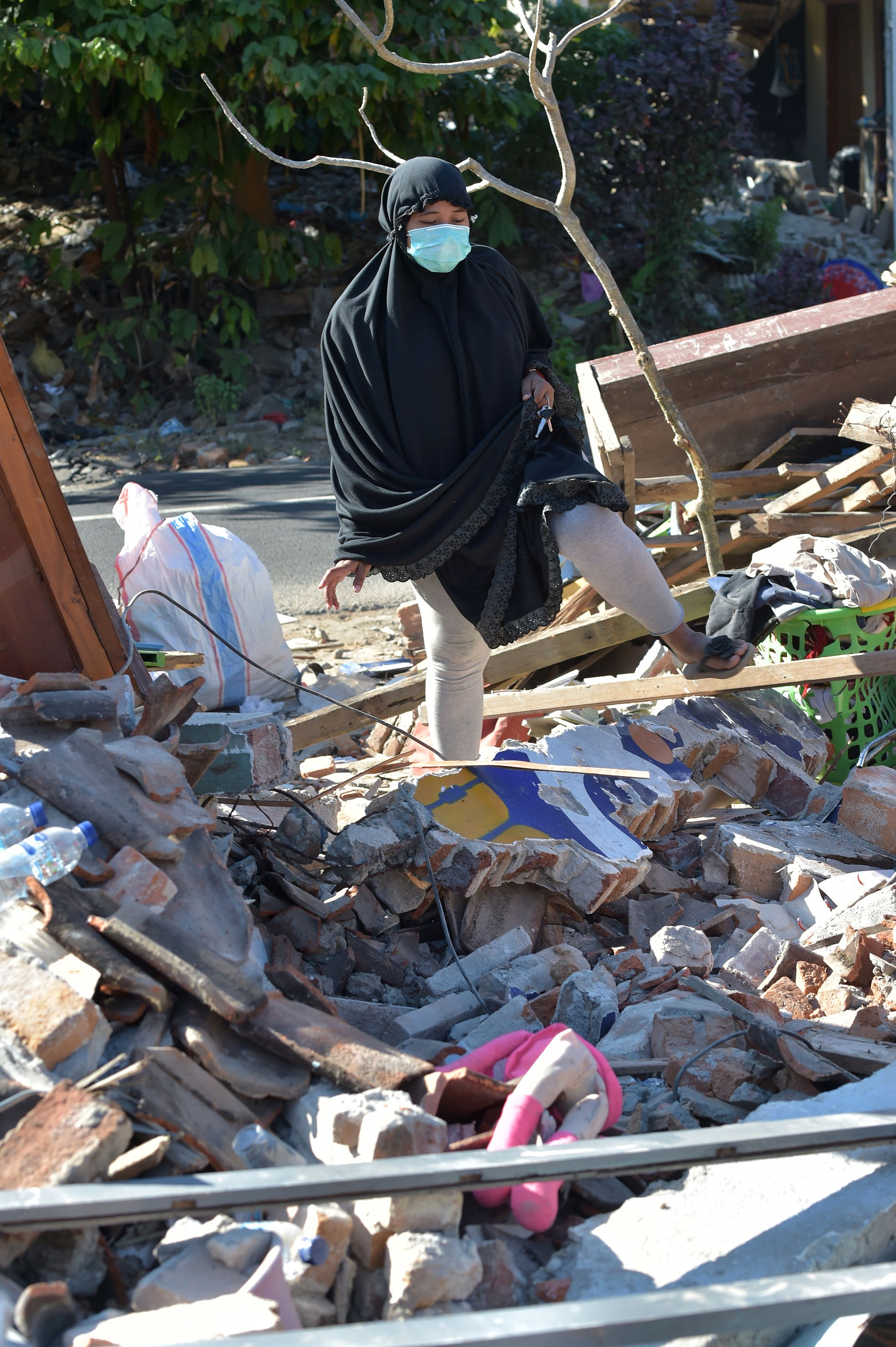 إمرأة تقف على أنقاض بيتها