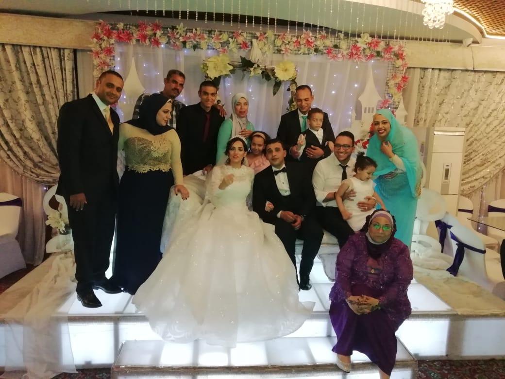 عائلة الزميل محمود محيى يلتقطون صورة تذكارية مع العروسان