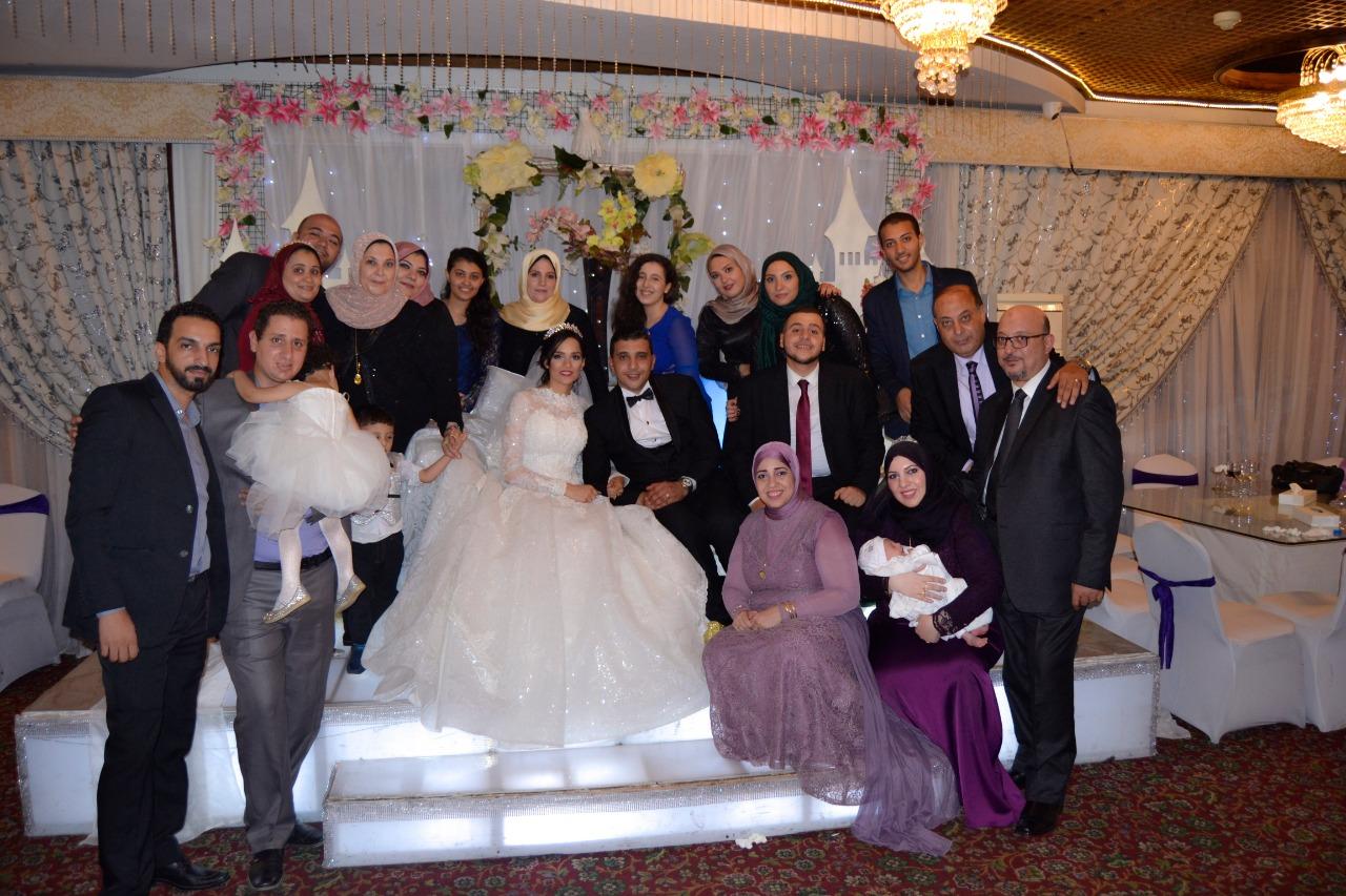 العروسان يلتقطان صورة تذكارية مع الأقرباء