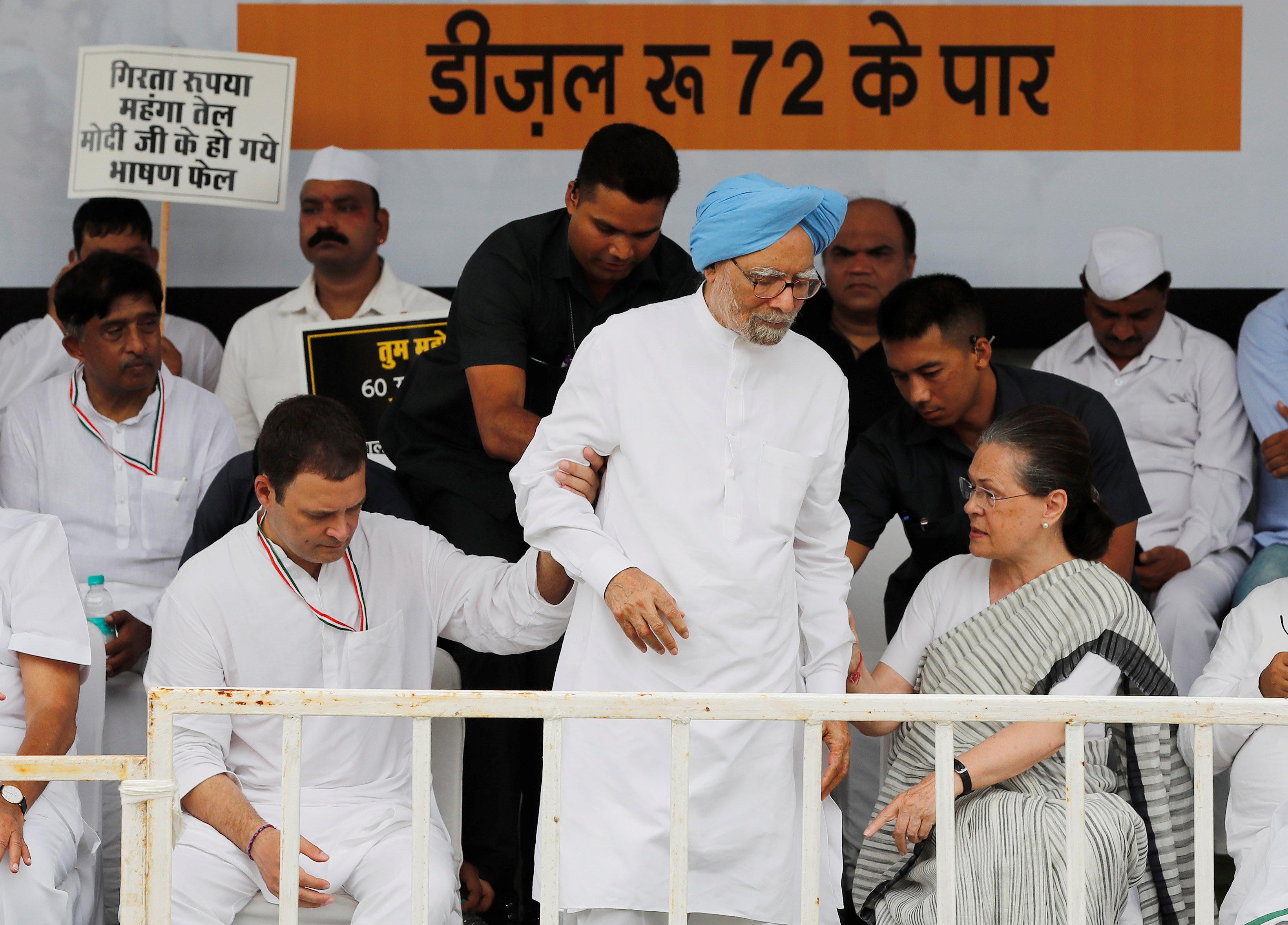 رئيس حزب المؤتمر وأمه وزعيم حزب سونيا غاندى يساعدان رئيس الوزراء الهندى السابق على الوقوف خلال احتجاج على أسعار البنزين