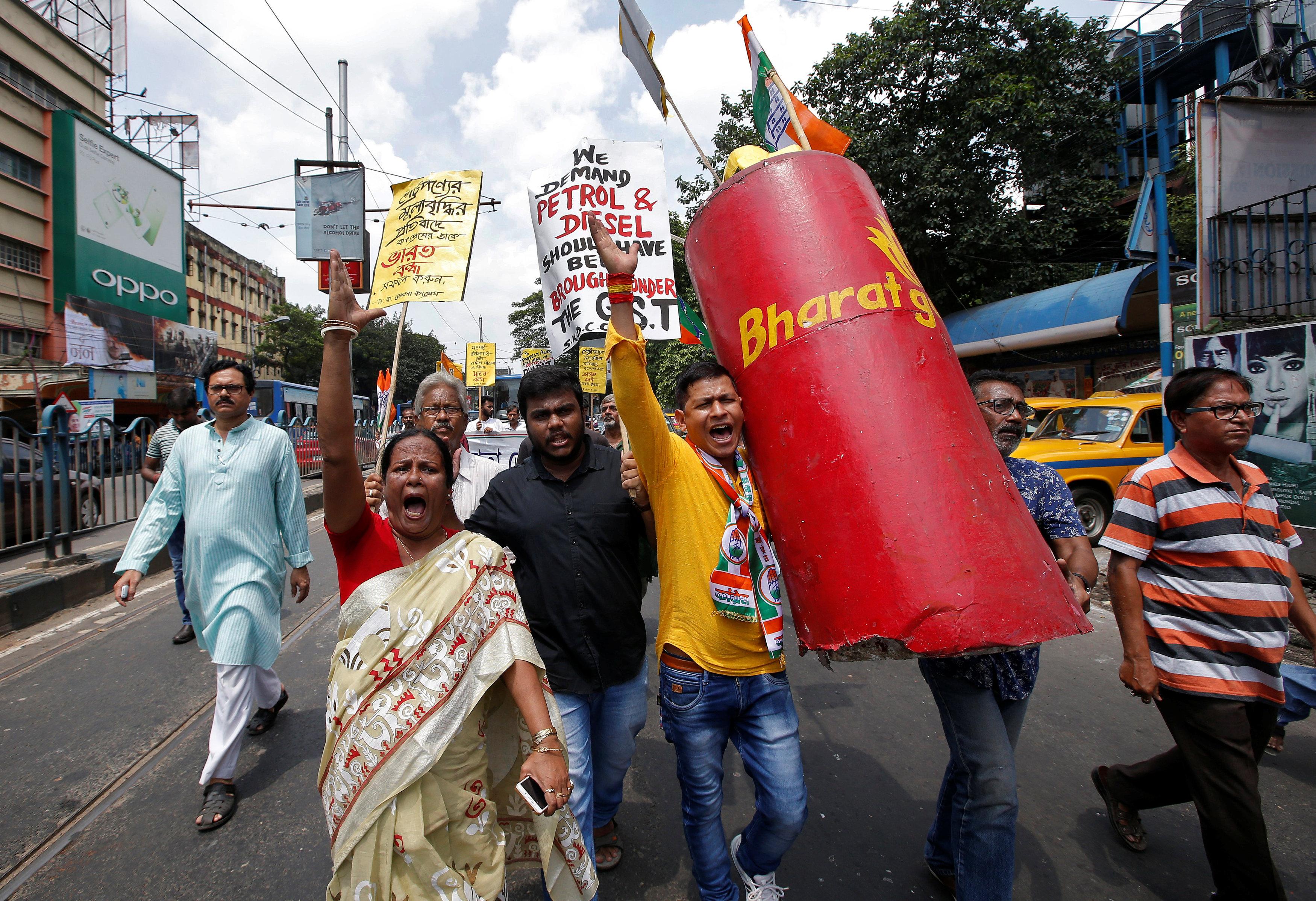 المعارضين فى الهند يهتفون بشعارات مناهضة للحكومة وهم يحملون نموذجا لأسطوانة غاز البترول المسال