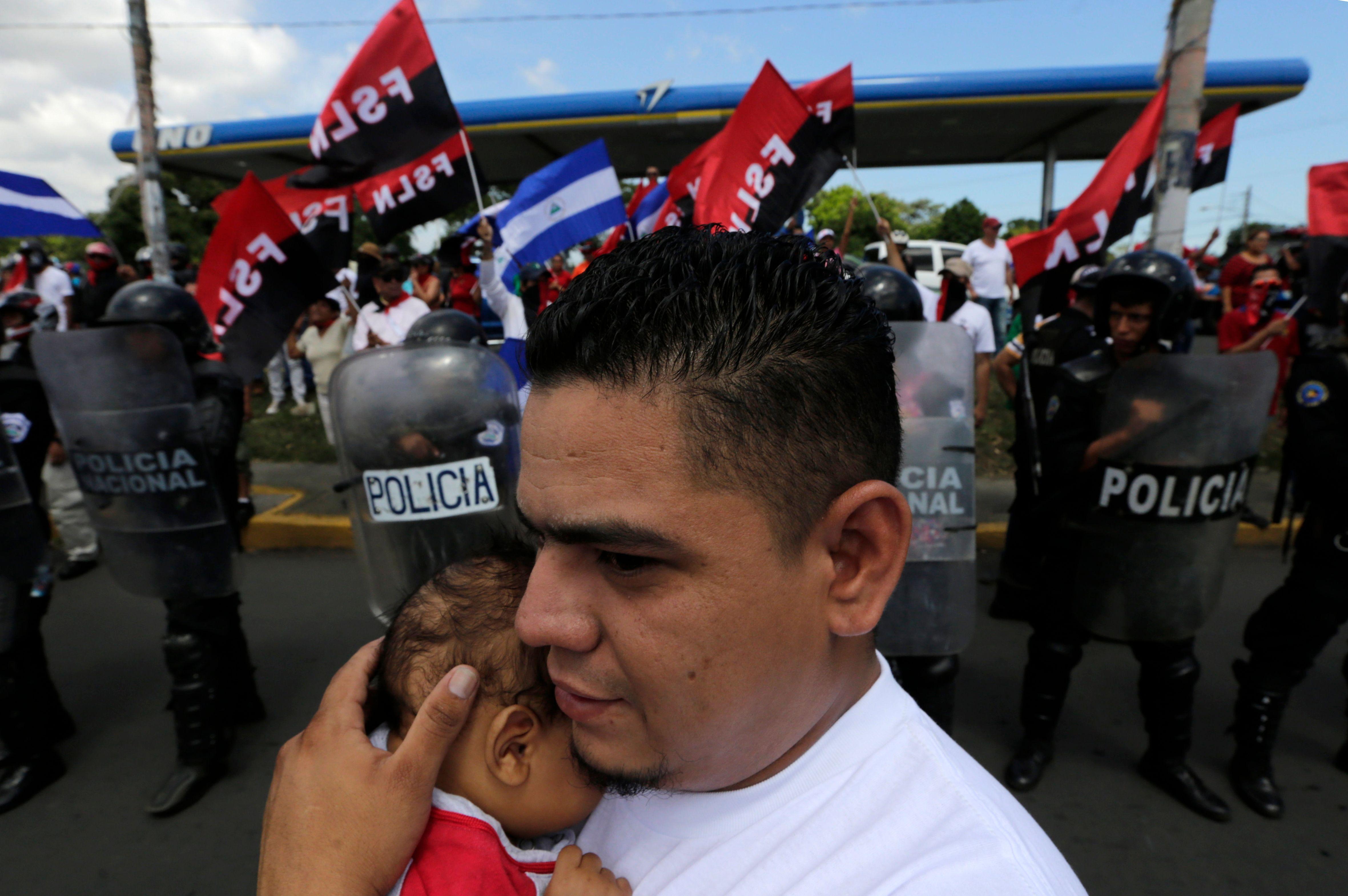 رجل يحمل طفل خلال الاحتجاجات