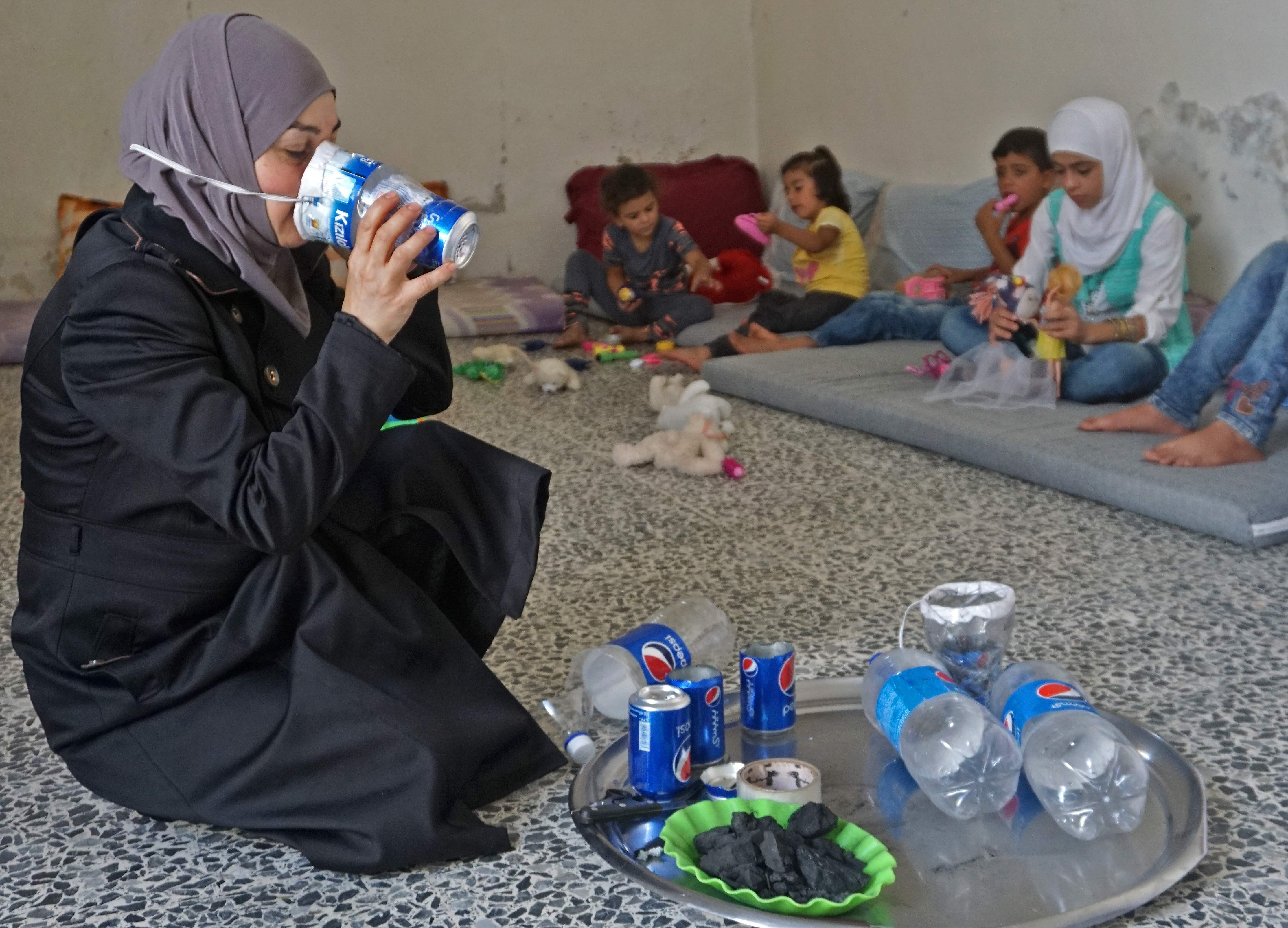 ام سورية تدرب اولادها على استخدام اقنعة الغاز