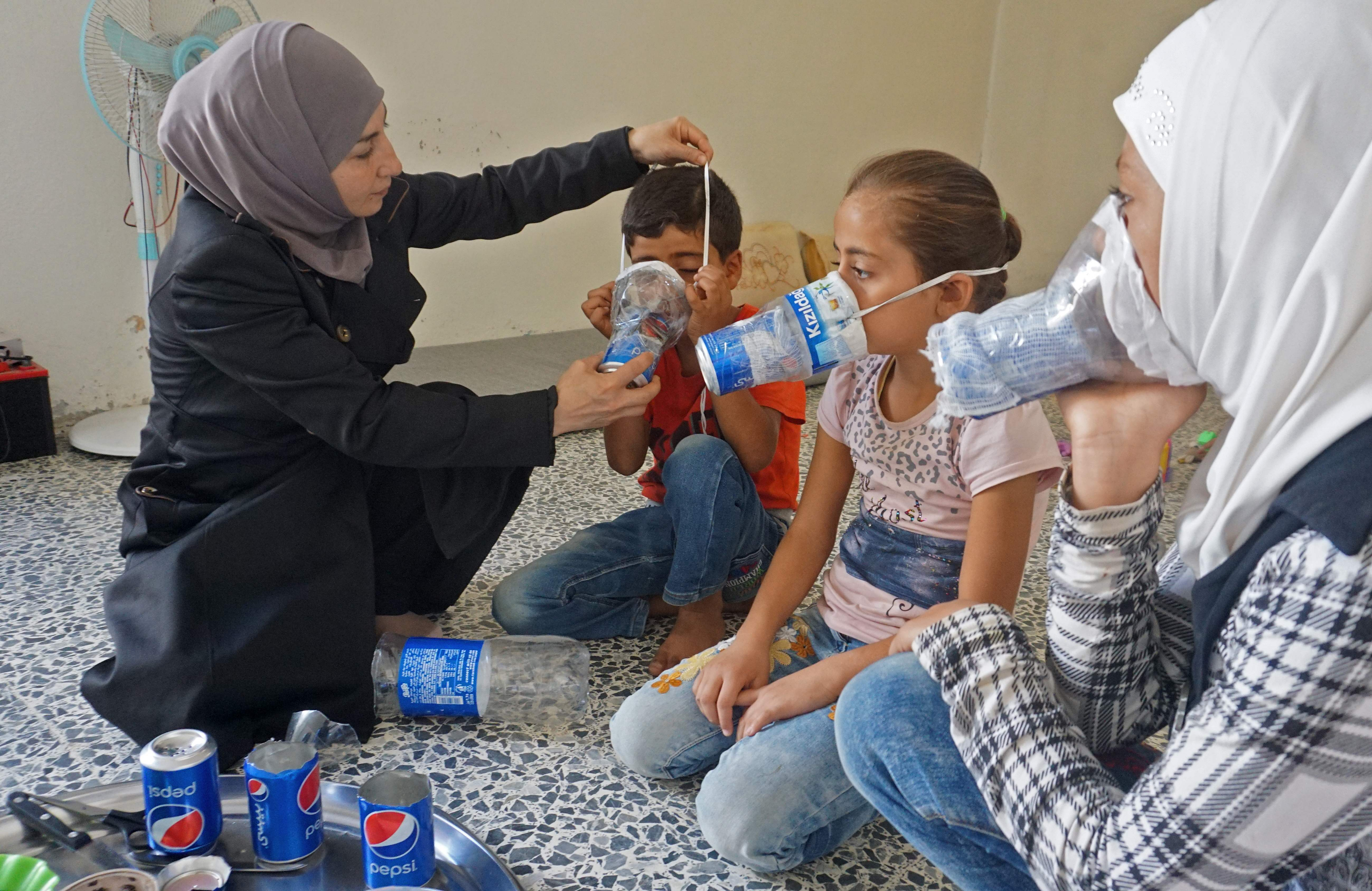 الام تساعد اطفالها على ارتداء اقنعة الغاز