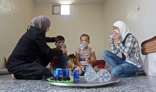 ام سورية تعد اقنعة الغاز لاطفالها من المواد الاولية