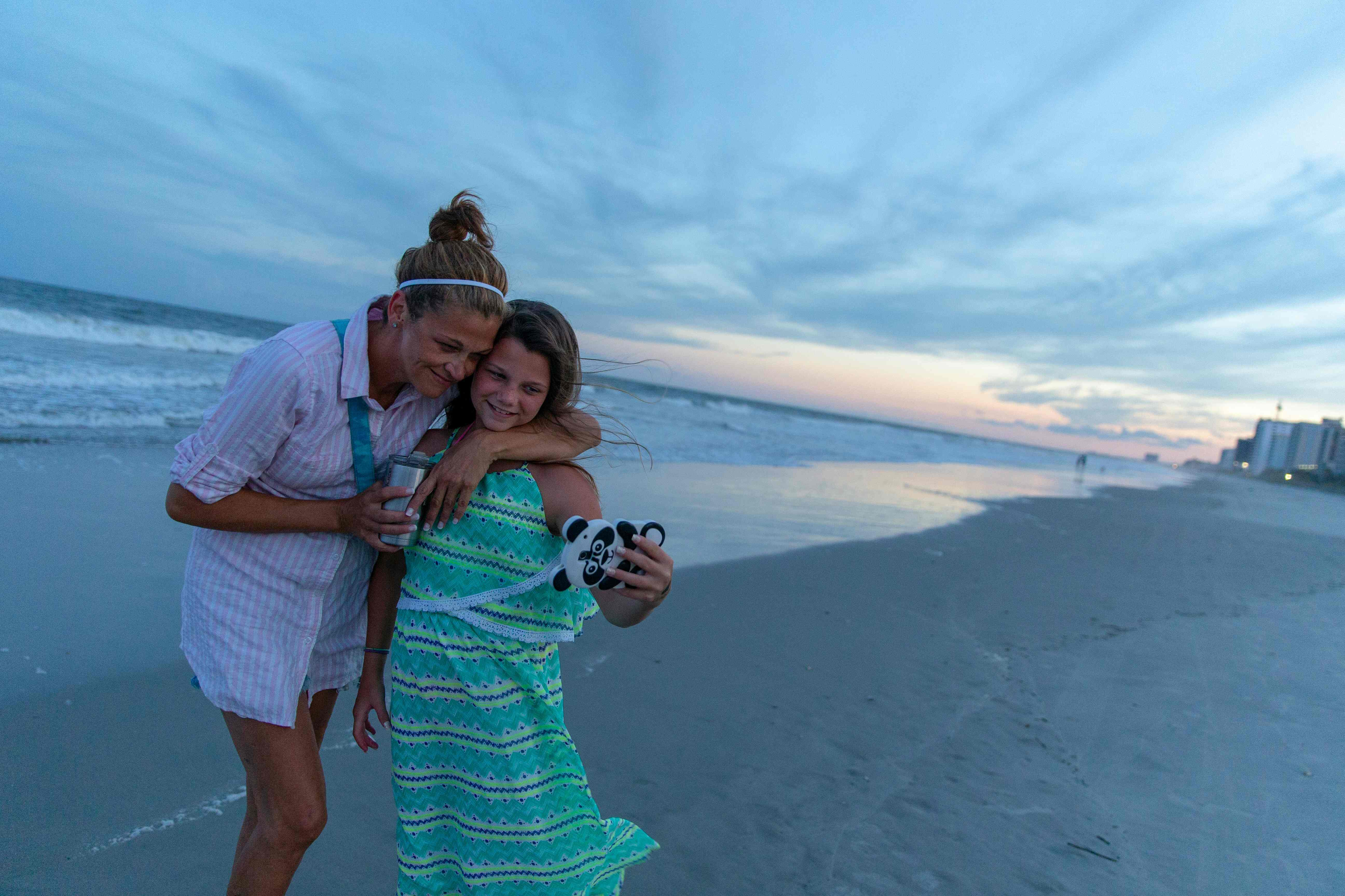 فتاة تلتقط صورة شخصية مع والدتها أثناء غروب الشمس فى ميرتل بيتش جنوب كارولينا