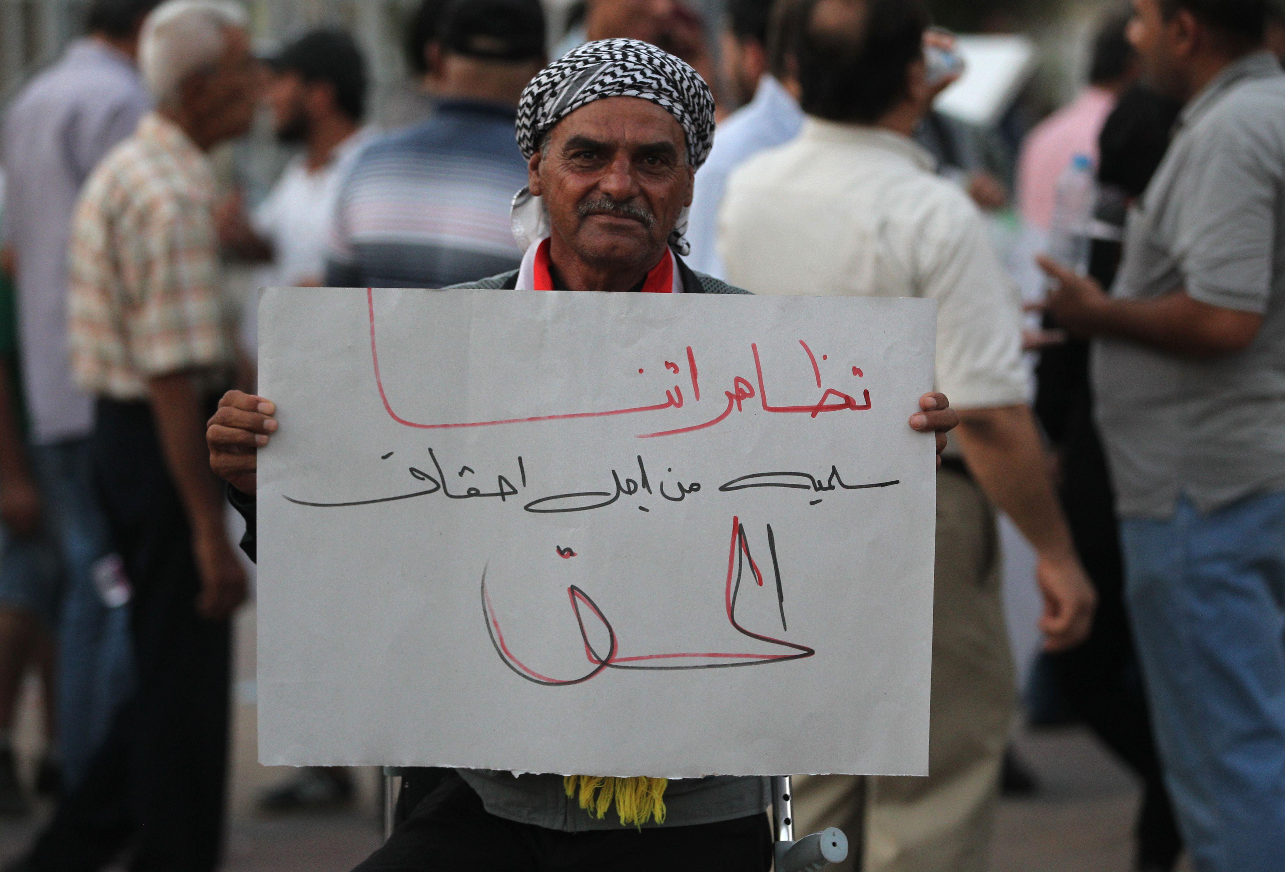 متظاهر يحمل لافتة